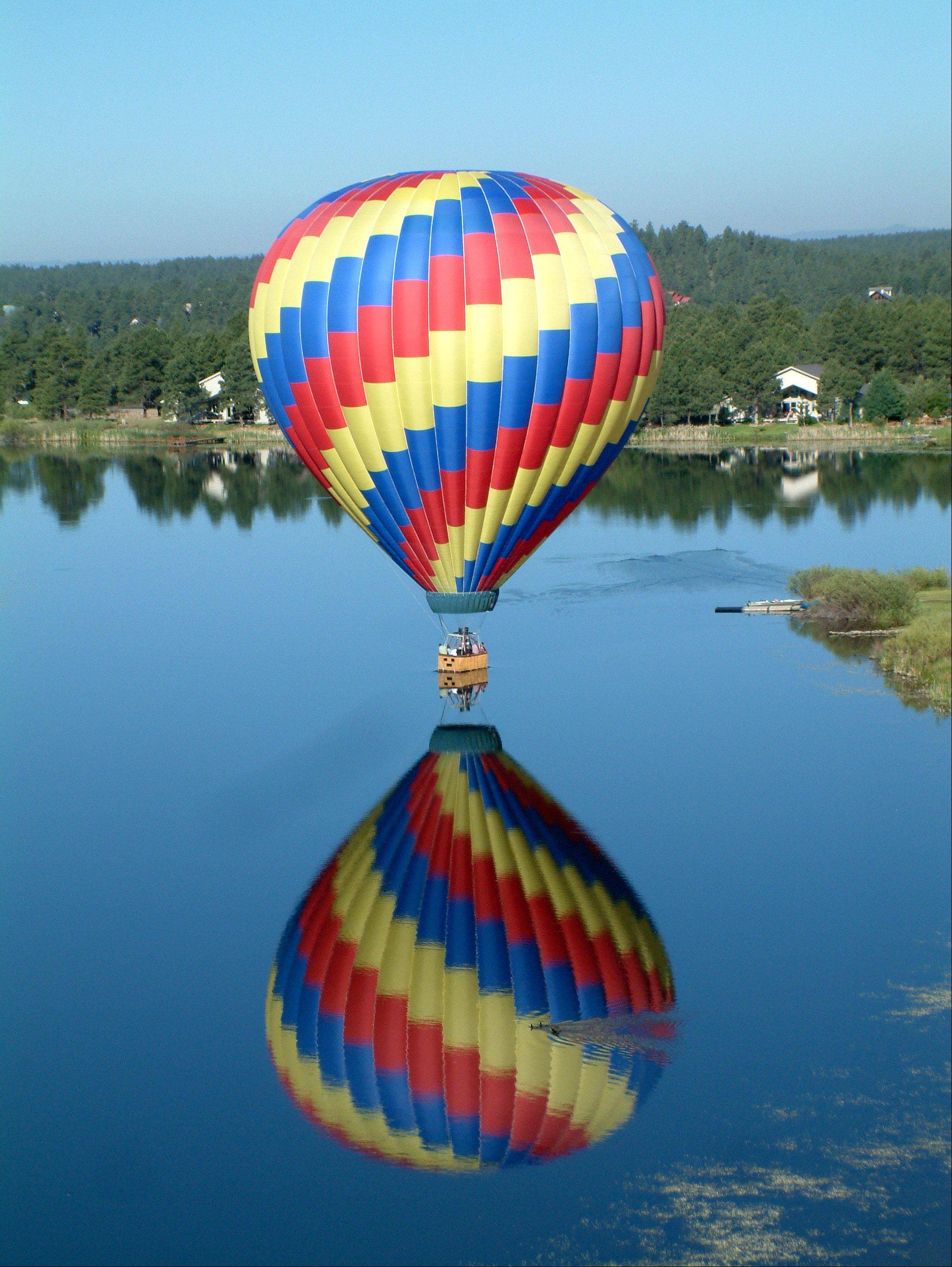 "This photo taken June in Pagosa Springs, Colorado on a hot-air balloon ride. My mom and I were in one balloon, and this was a view of the other balloon doing a ""splash & dash"" in the lake. Our turn was next!"