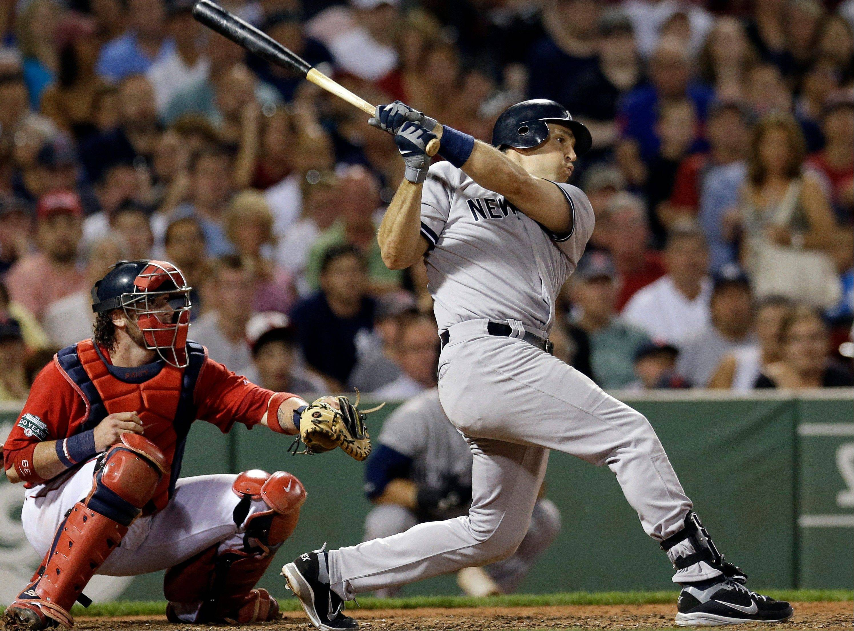 New York's Mark Teixeira follows through on a two-run triple as Red Sox catcher Jarrod Saltalamacchia watches in the seventh inning Friday in Boston.