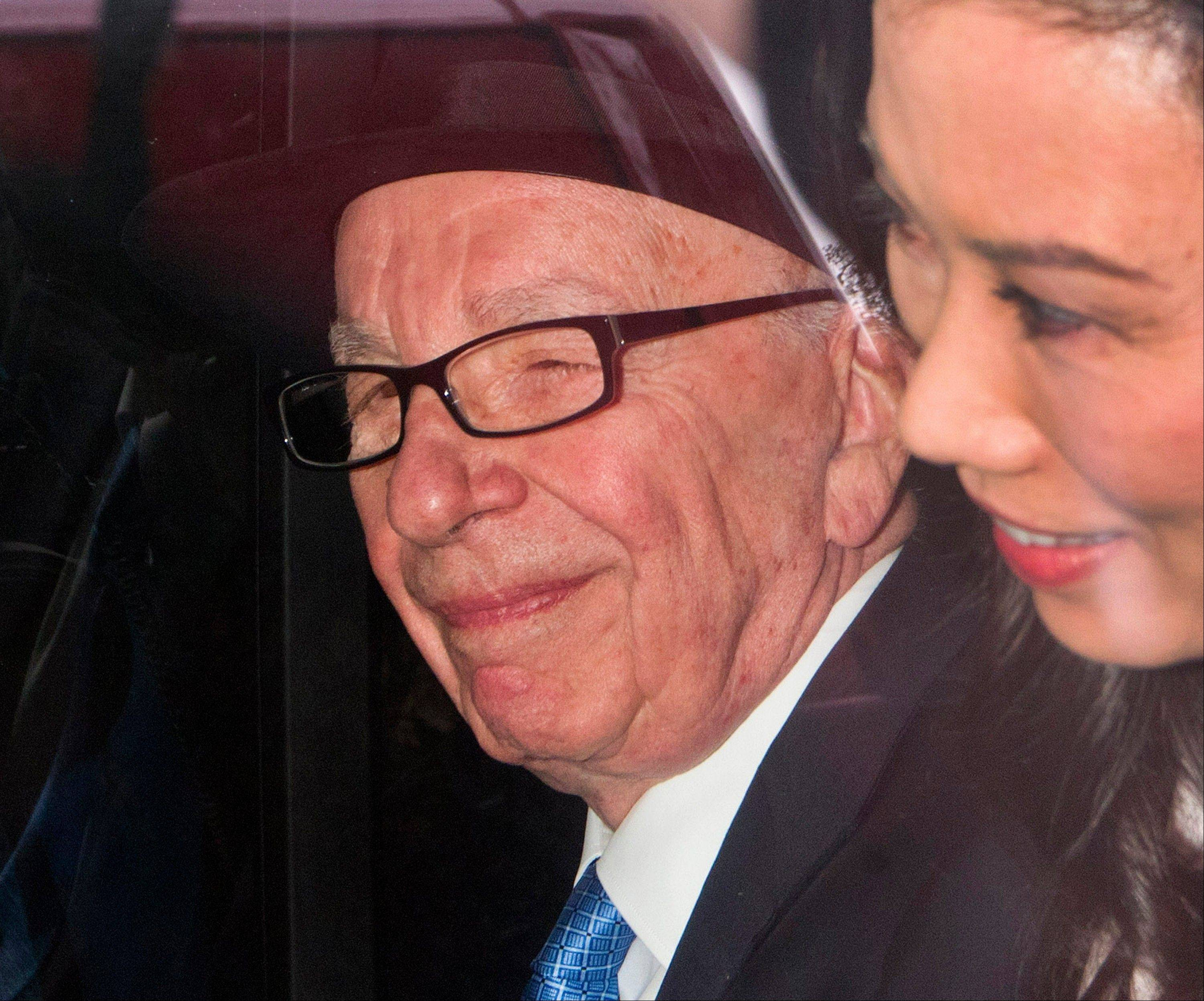 News Corp. chairman Rupert Murdoch and his wife Wendi Deng leave the High Court in London.