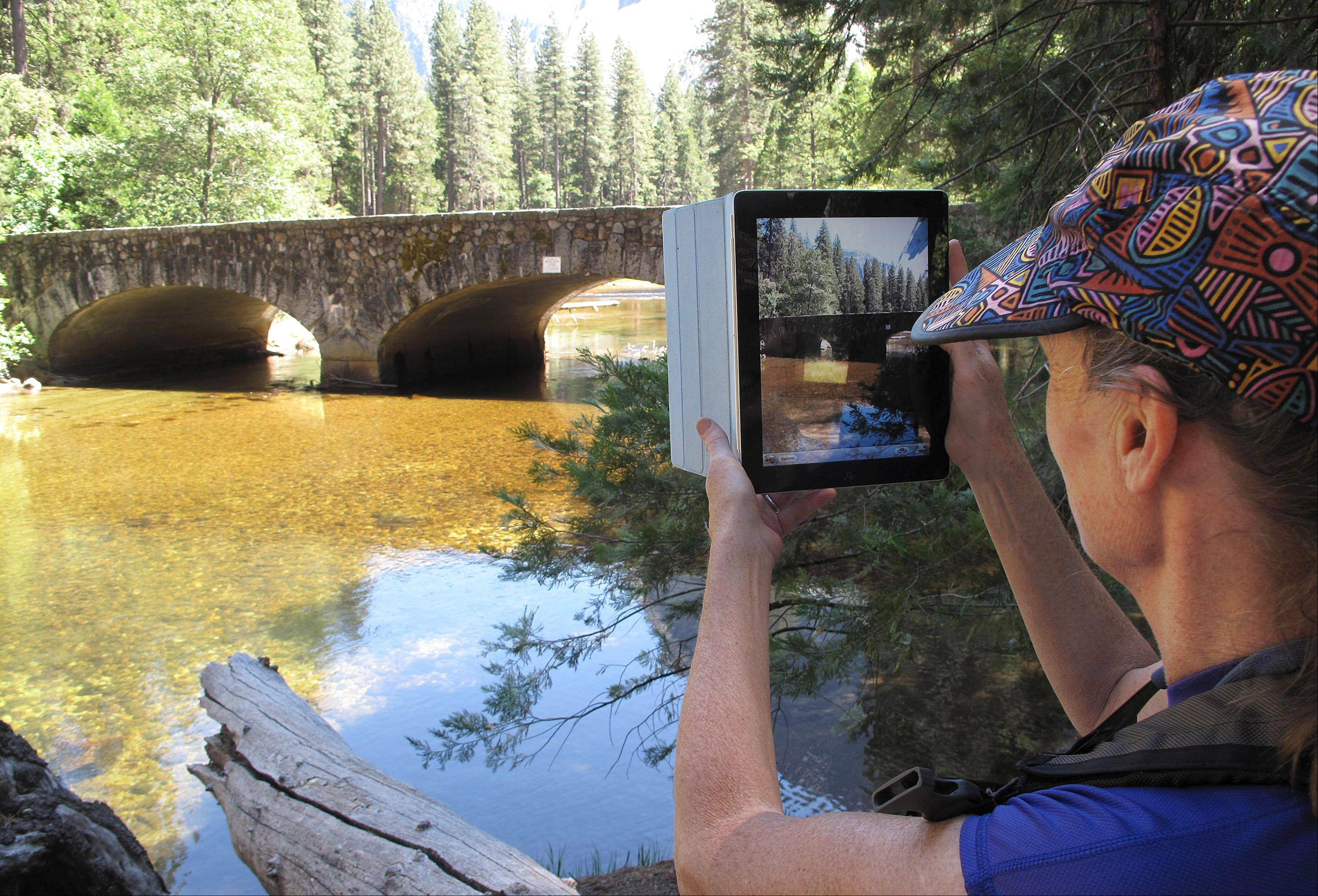 Christa Danielson of Eugene, Ore., stops to take a photo of Ahwahnee Bridge, one of three historic bridges with abutments in the Merced River that could be removed under plans being developed to restore natural flows, in Yosemite Valley, Calif.
