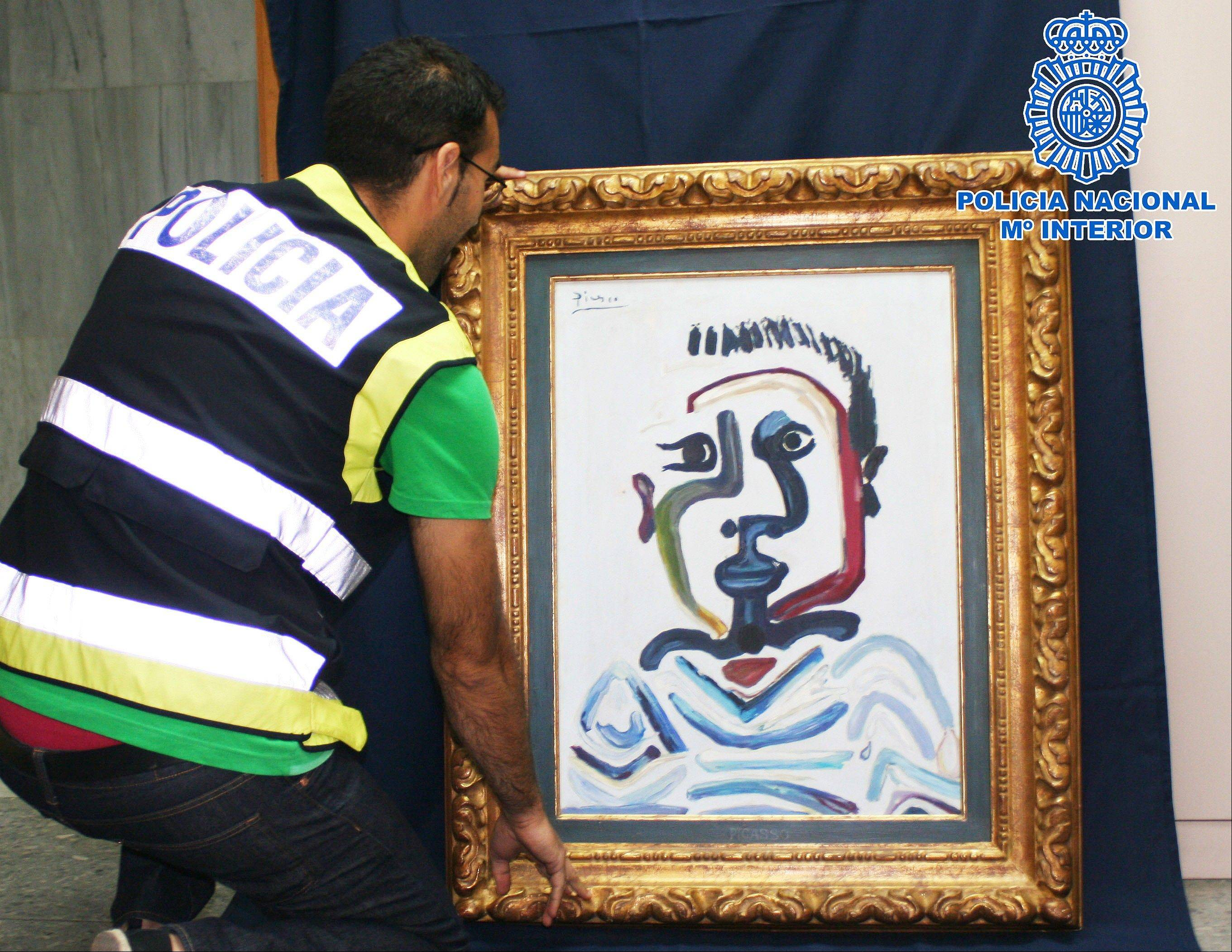 A Spanish police officer holds a forged Pablo Picasso oil painting in Sevilla Saturday, July 7. The Interior Ministry says National Police have arrested four people for trying to sell a forged Pablo Picasso oil painting for up to $1.5 million. The canvas, a counterfeit version of a 1964 work called �The bust of Jeune Garcon� was accompanied by false authenticity documents.