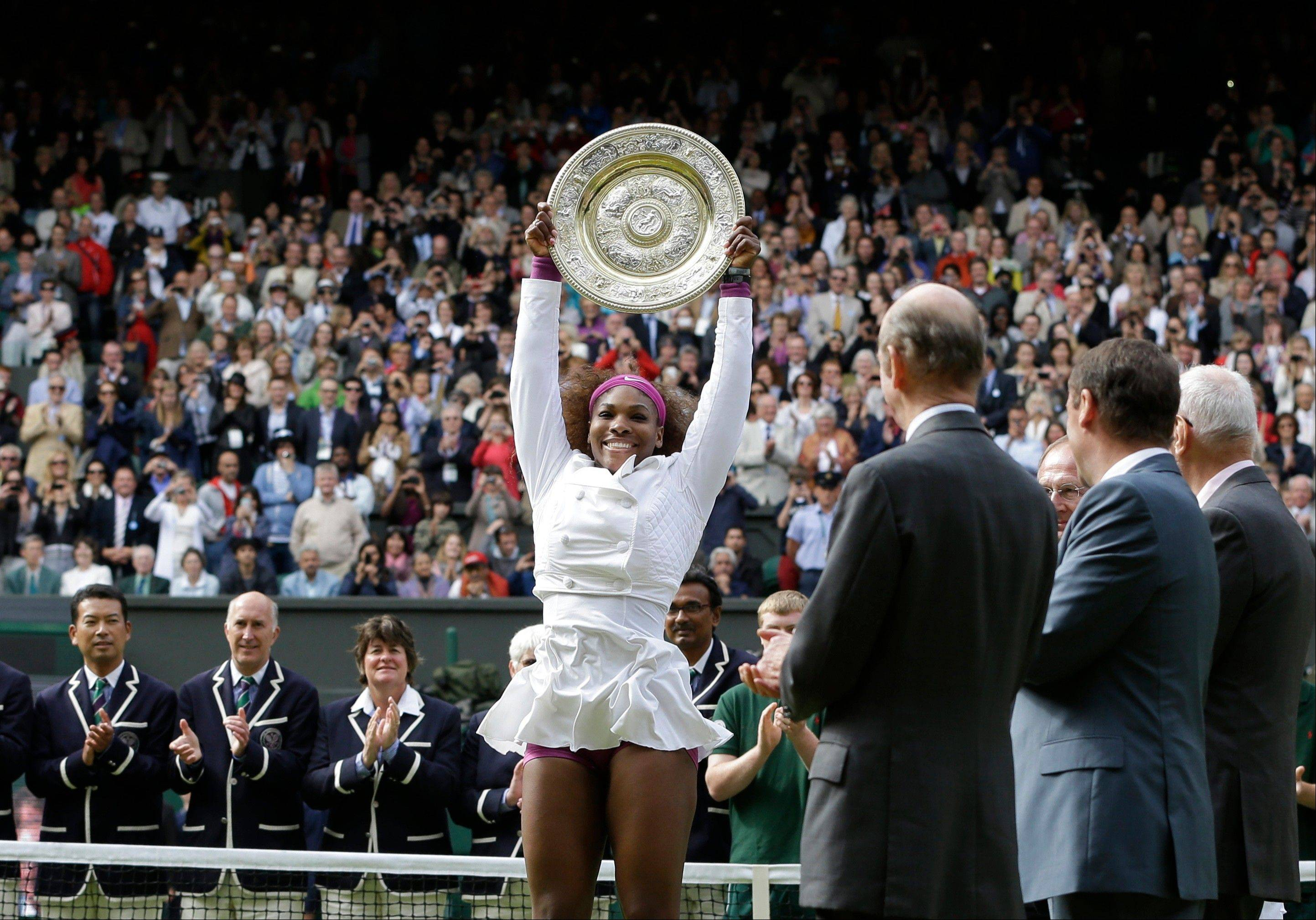Serena Williams of the United States, center, celebrates with the trophy after defeating Agnieszka Radwanska of Poland to win the women's final match at the All England Lawn Tennis Championships at Wimbledon, England, Saturday, July 7.