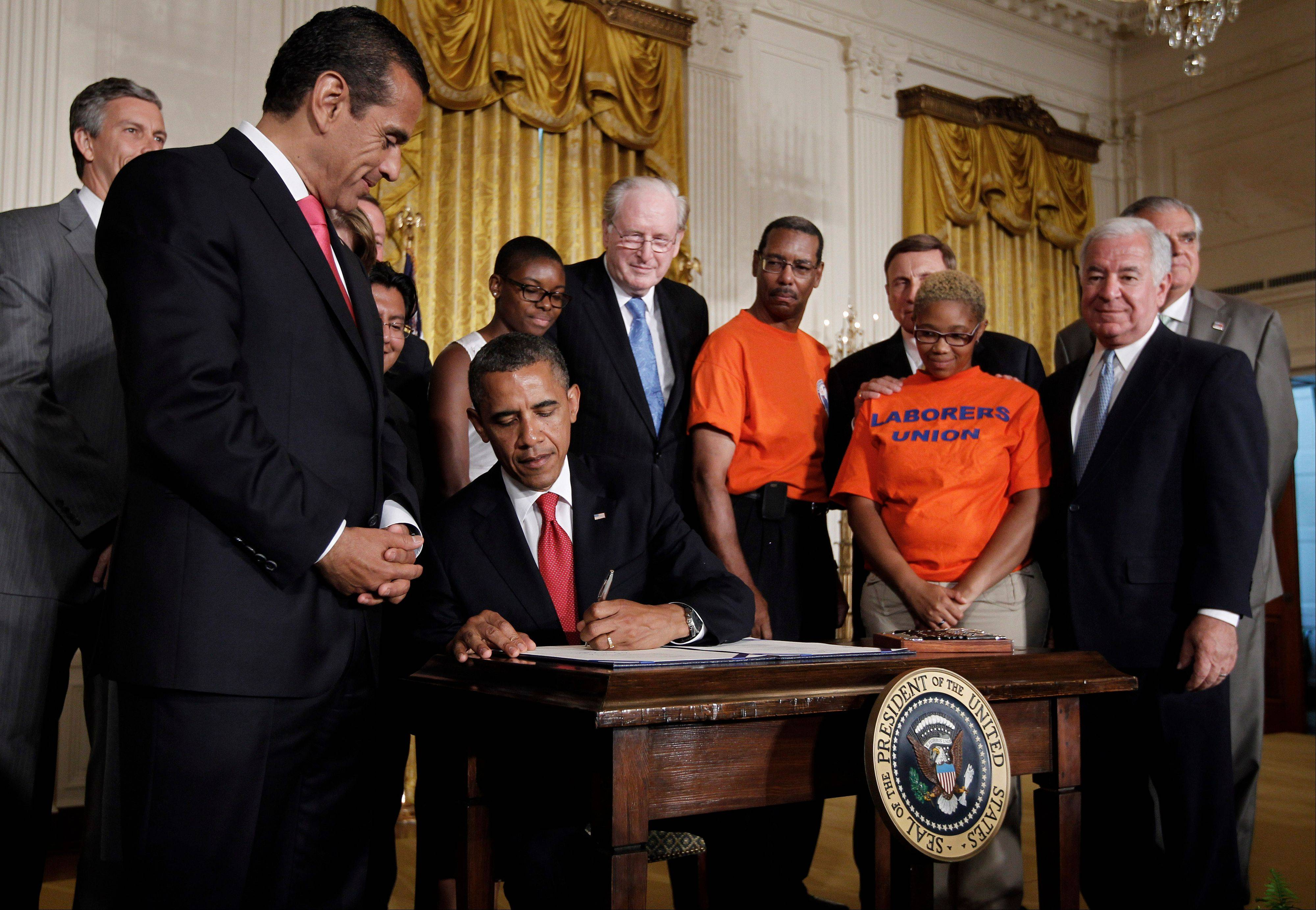 President Barack Obama, flanked by unemployed construction workers, college students and members of Congress, signs HR4348, the Surface Transportation Bill, during a ceremony Friday in the East Room of the White House in Washington. The bill maintains prevents interest rate increases on new loans to millions of college students.