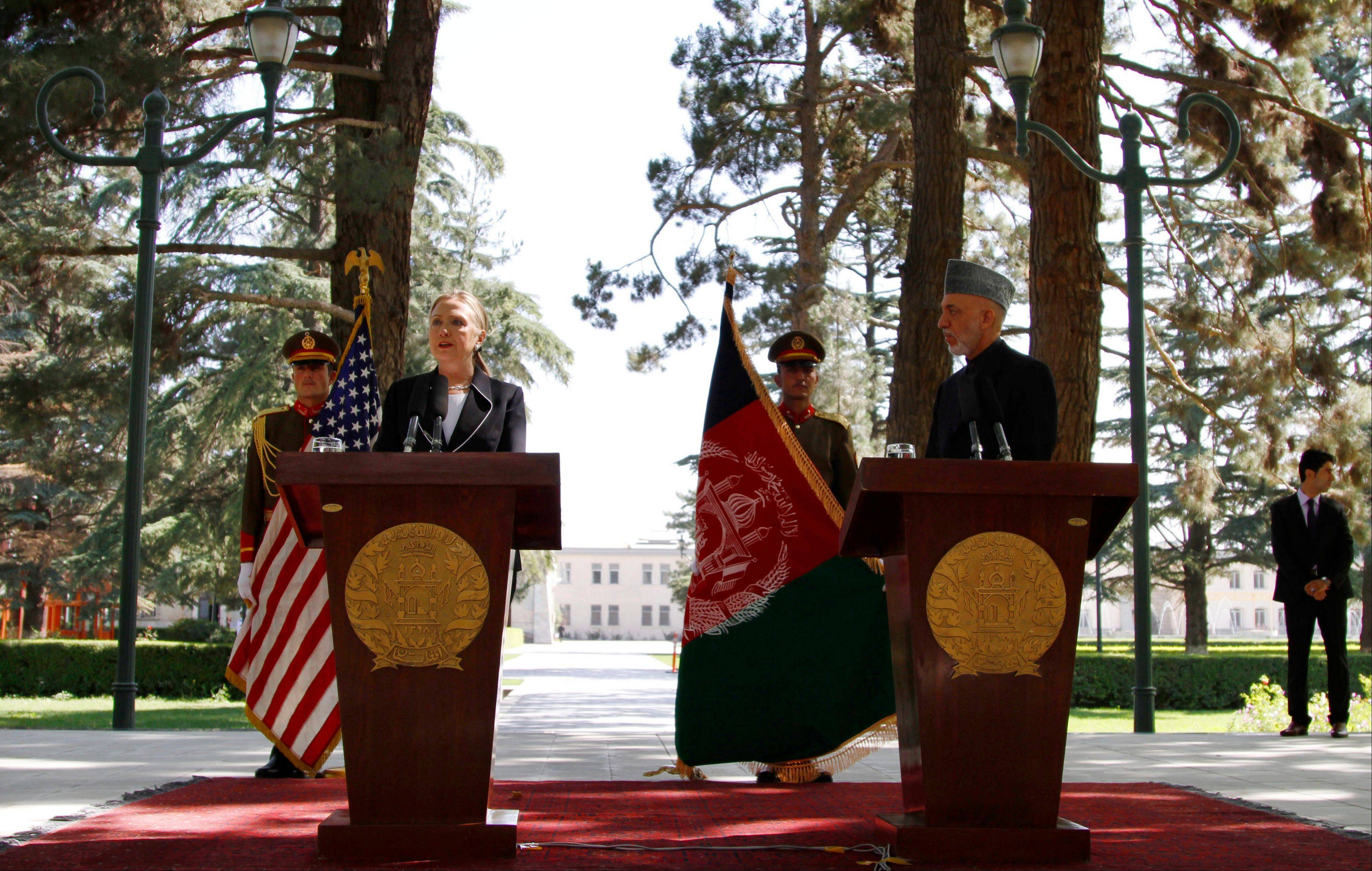 U.S. Secretary of State Hillary Rodham Clinton speaks as Afghan President Hamid Karzai listens during a joint press conference Saturday at the Presidential Palace.