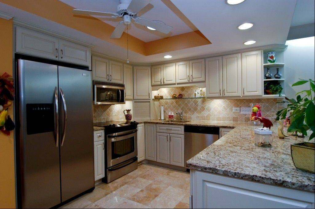 The updated kitchen has a marble floor and stainless steel appliances.