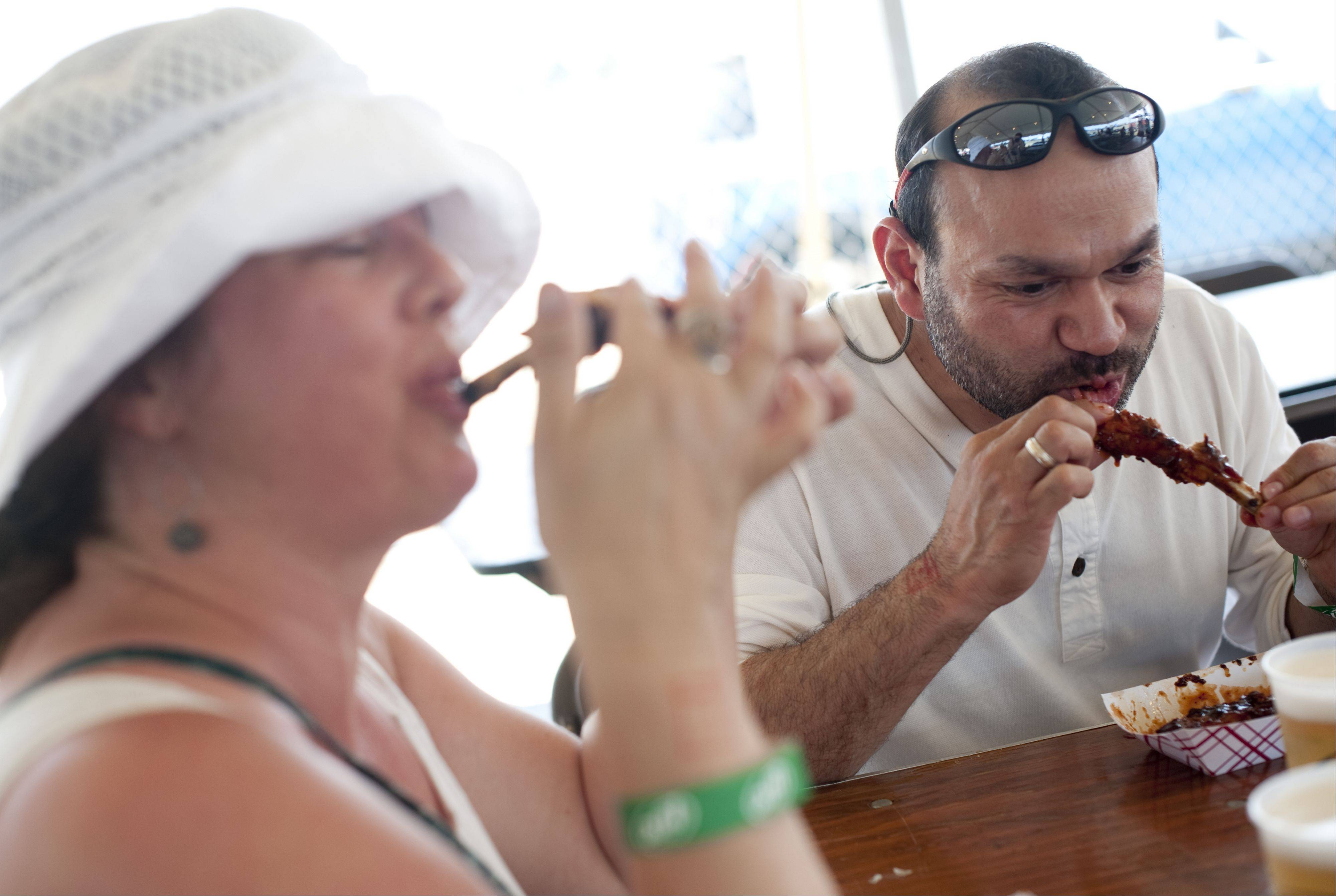 Linda Meyer and Miguel Bautista of Cary enjoy ribs from Armadillo's BBQ Saturday at the Lake in the Hills Rockin' Ribfest in Sunset Park.