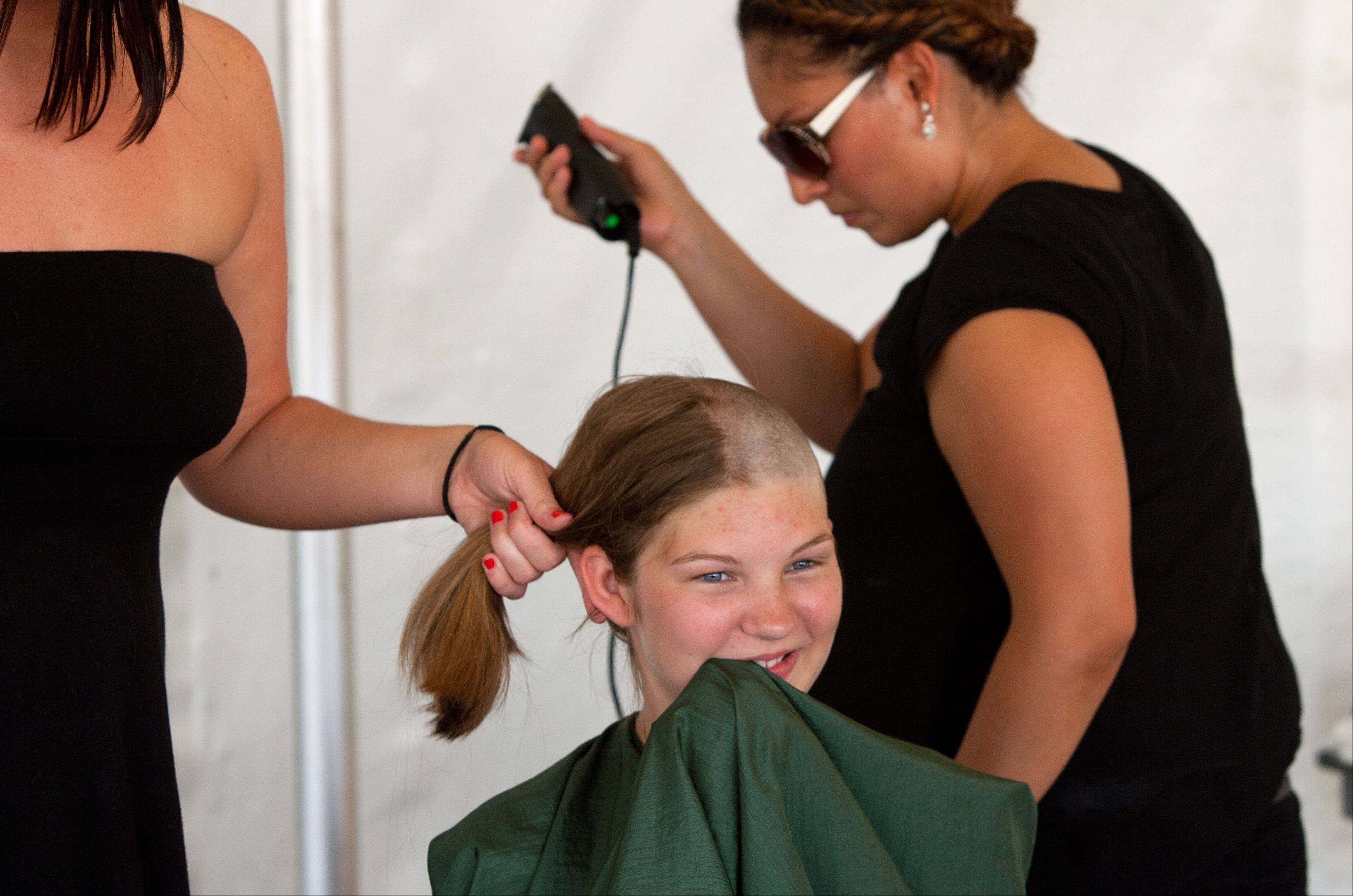 Jessica Nichols, 11, of Downers Grove, gets her head shaved for a donation to the St. Baldrick's Foundation Saturday at the Taste of Lombard courtesy of Cristy Vazquez of Paul Mitchell, The School in Chicago.