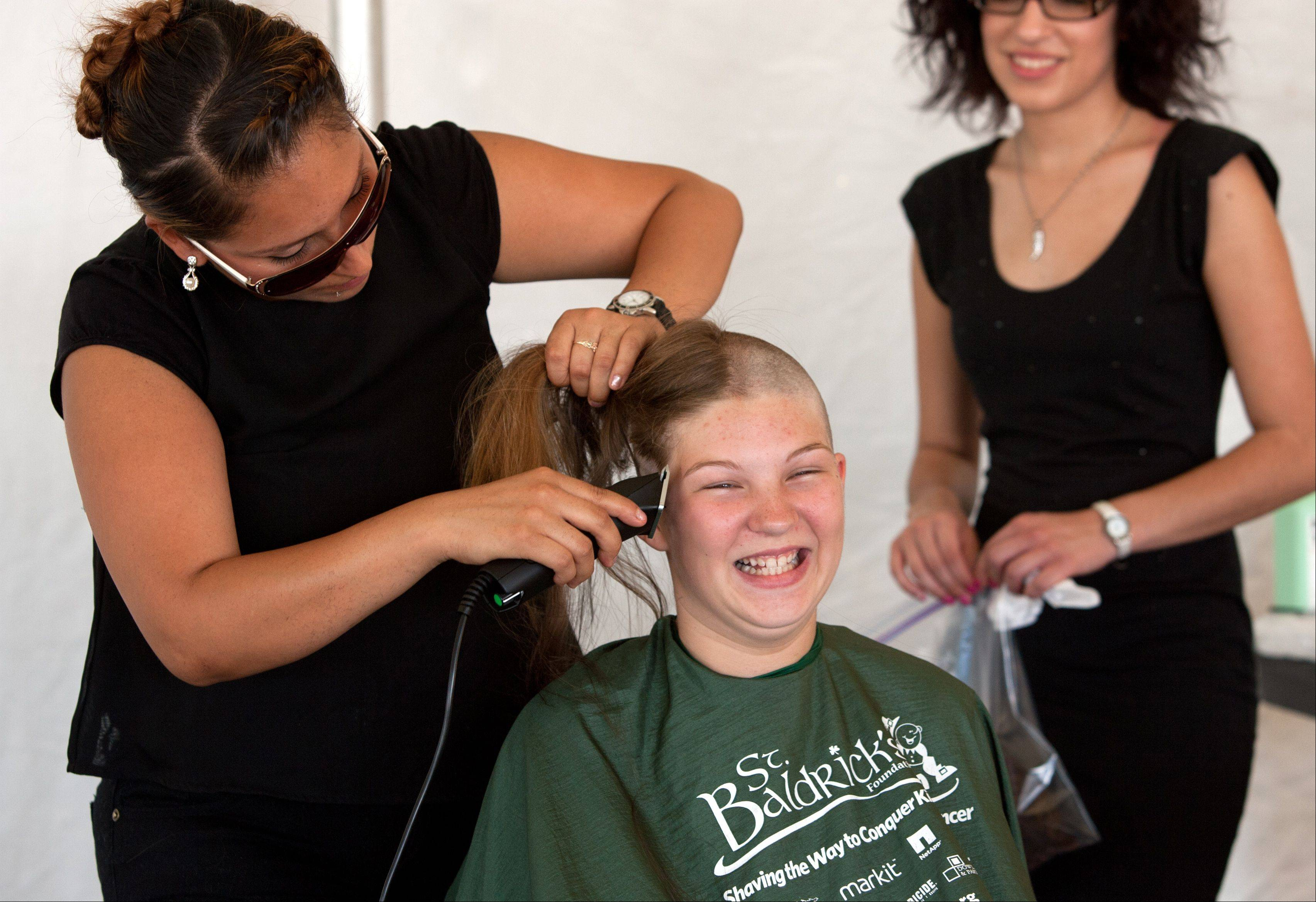 Jessica Nichols, 11, of Downers Grove, enjoys her first head-shaving experience Saturday at the Taste of Lombard as she participates in a St. Baldrick's Foundation shave-a-thon. Cristy Vazquez of Paul Mitchell, The School in Chicago, was among hairdressers who volunteered to do the shaving.