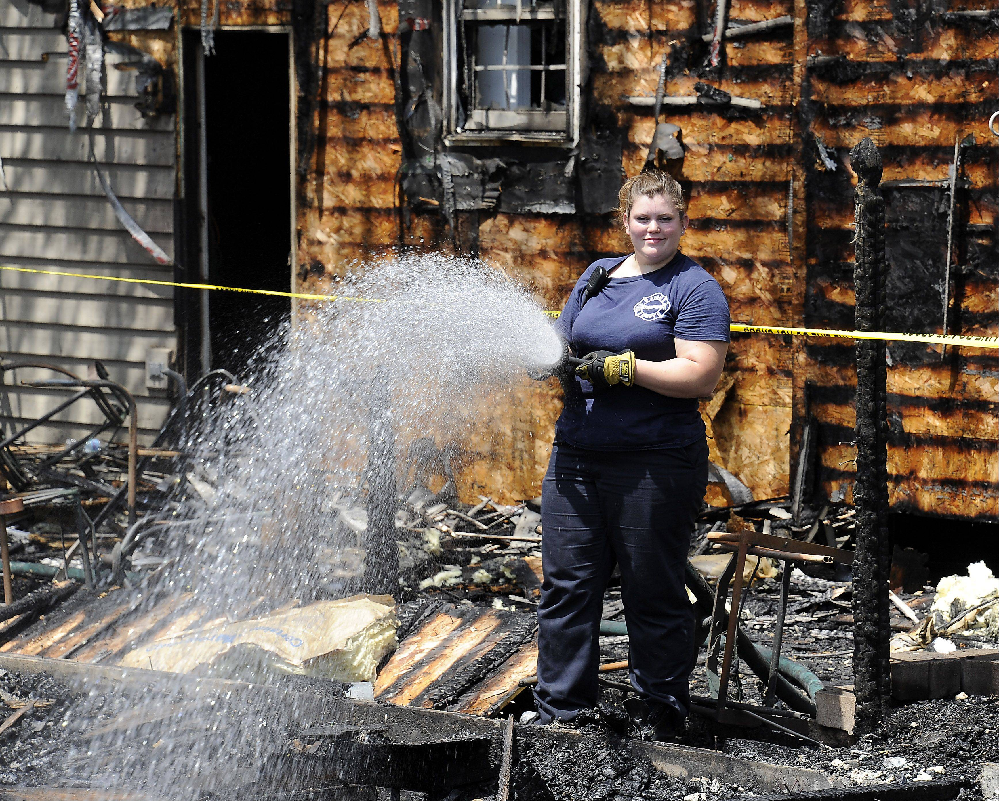 Streamwood firefighter/paramedic Lisa Meyer sprays water on the smoldering remains of a house fire in the 100 block of Grey Fox Court in Streamwood on Saturday.