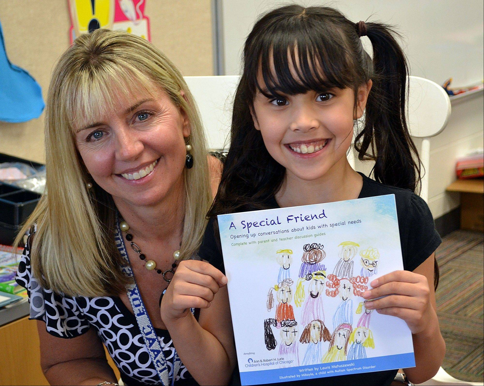 "Author Laura Matuszewski, left, poses with illustrator Mikayla Crow, right, with the first copy of the book ""A Special Friend""."