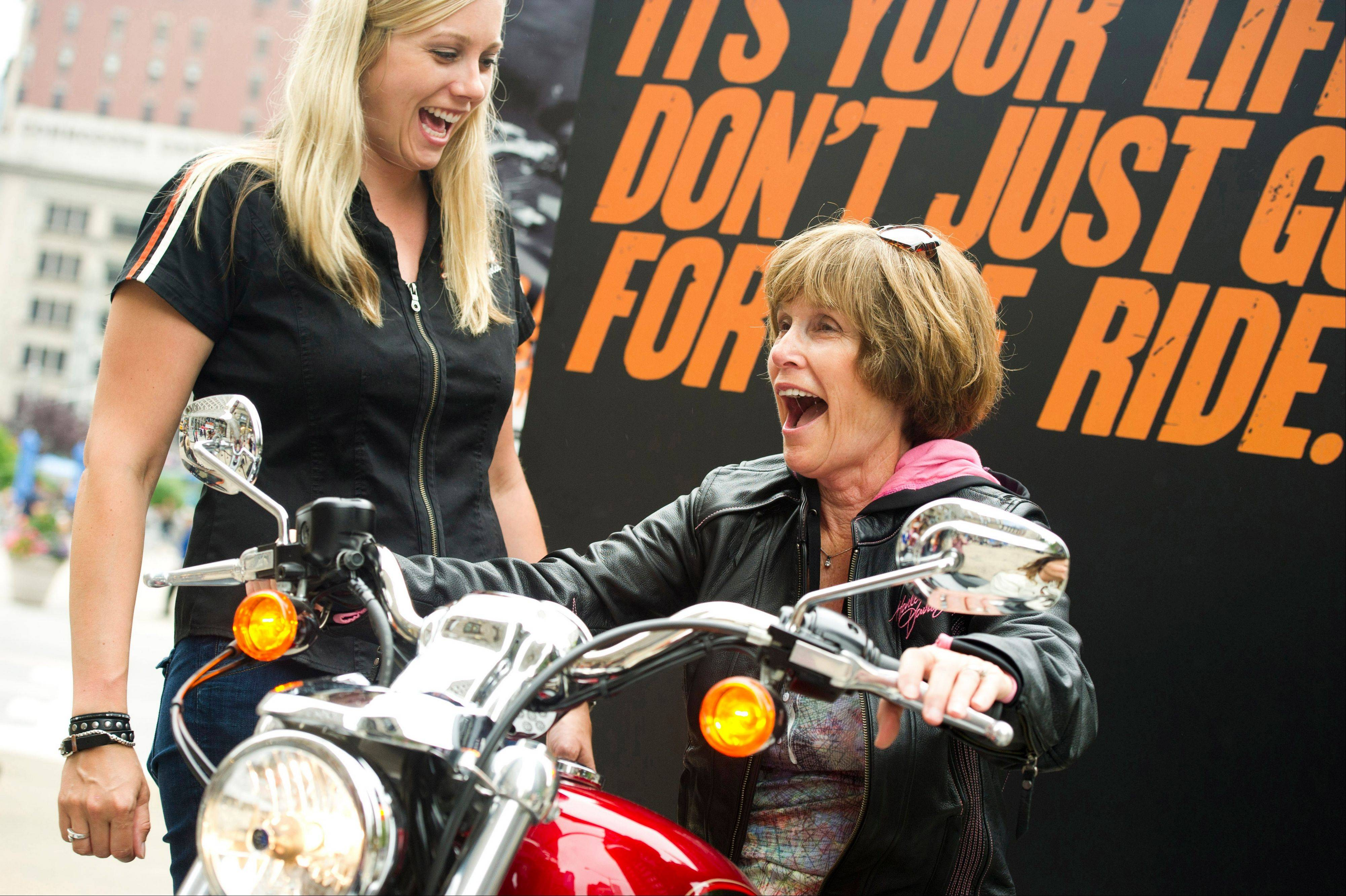 Harley-Davidson representative Dana Wilke, left, smiles as Nancy Dilley, 68, of Overland Park, Kan., learns the basics while test riding a motorcycle in New York on June 13. Harley-Davidson, based in Milwaukee, is the market leader in sales to women. The company travels around the country offering training and safety tips for women.