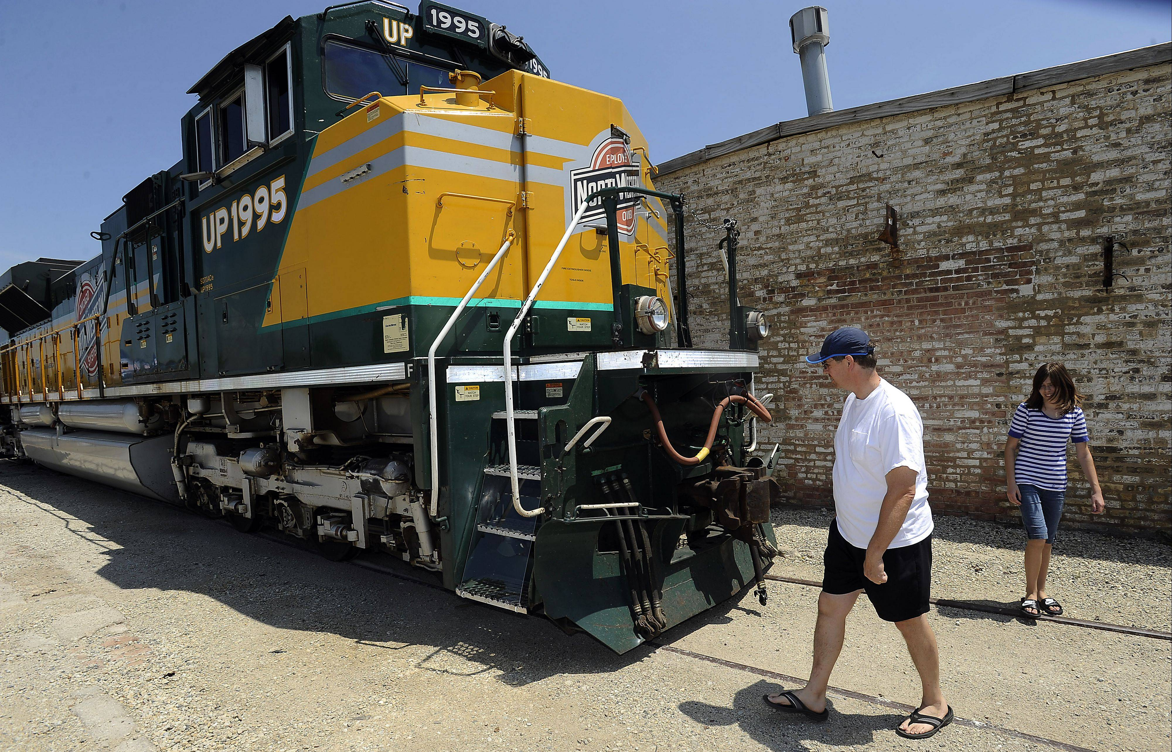 Train fanatic Jim Fitzgerald and his daughter Katie,12, check out Union Pacfic engine 1995 at the Arlington Heights Fontier Days on Saturday. The chance for people to get up close and personal with a locomotive fit with the train theme of the village's 125th anniversary. The engine carries the insignia of the Chicago & North Western Railway, which merged with Union Pacific in 1995. The C&NW Heritage locomotive is a working unit, and was painted in C&NW colors in 2006.