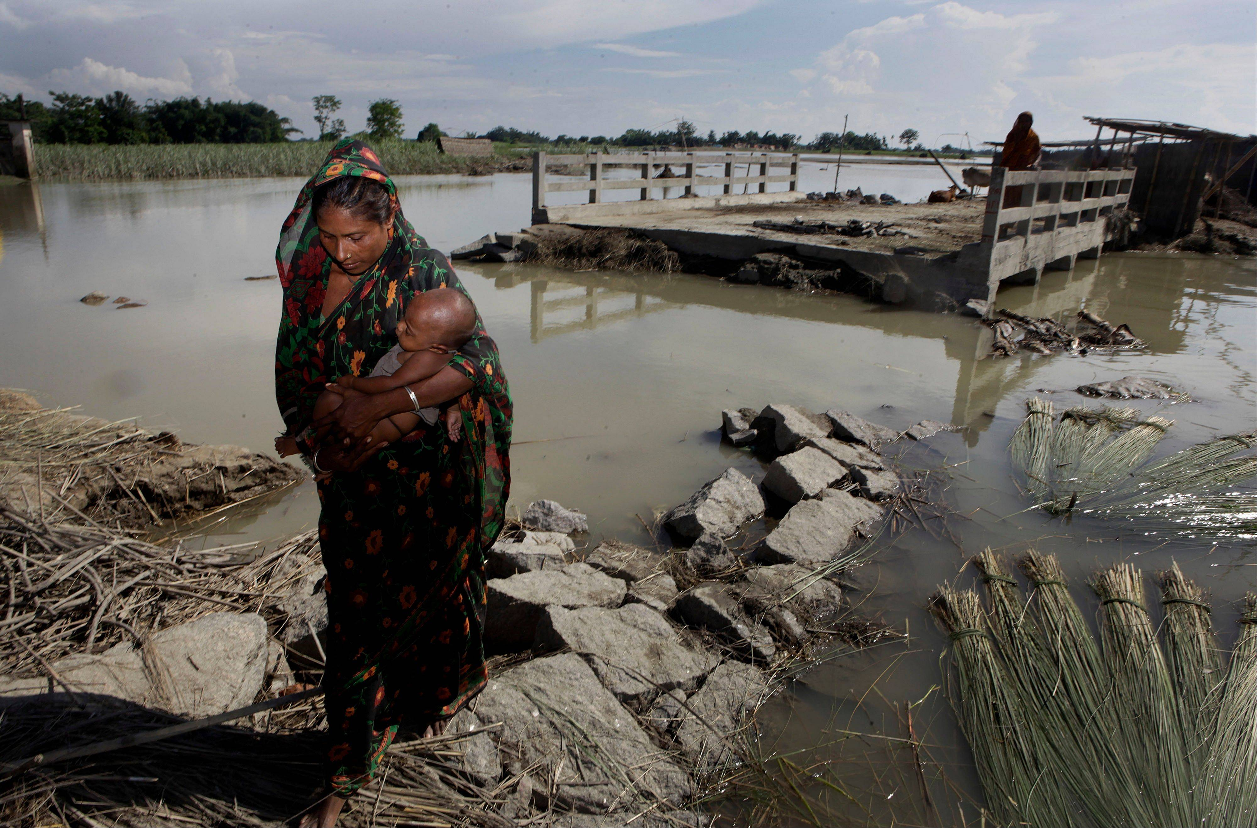A woman carries her baby as she walks past a bridge that was washed away in the recent monsoon floods in Deeghal Ati village in the northeastern Indian state of Assam on Sunday. About half of the 2.2 million people who were displaced remain in makeshift shelters or with relatives or friends.