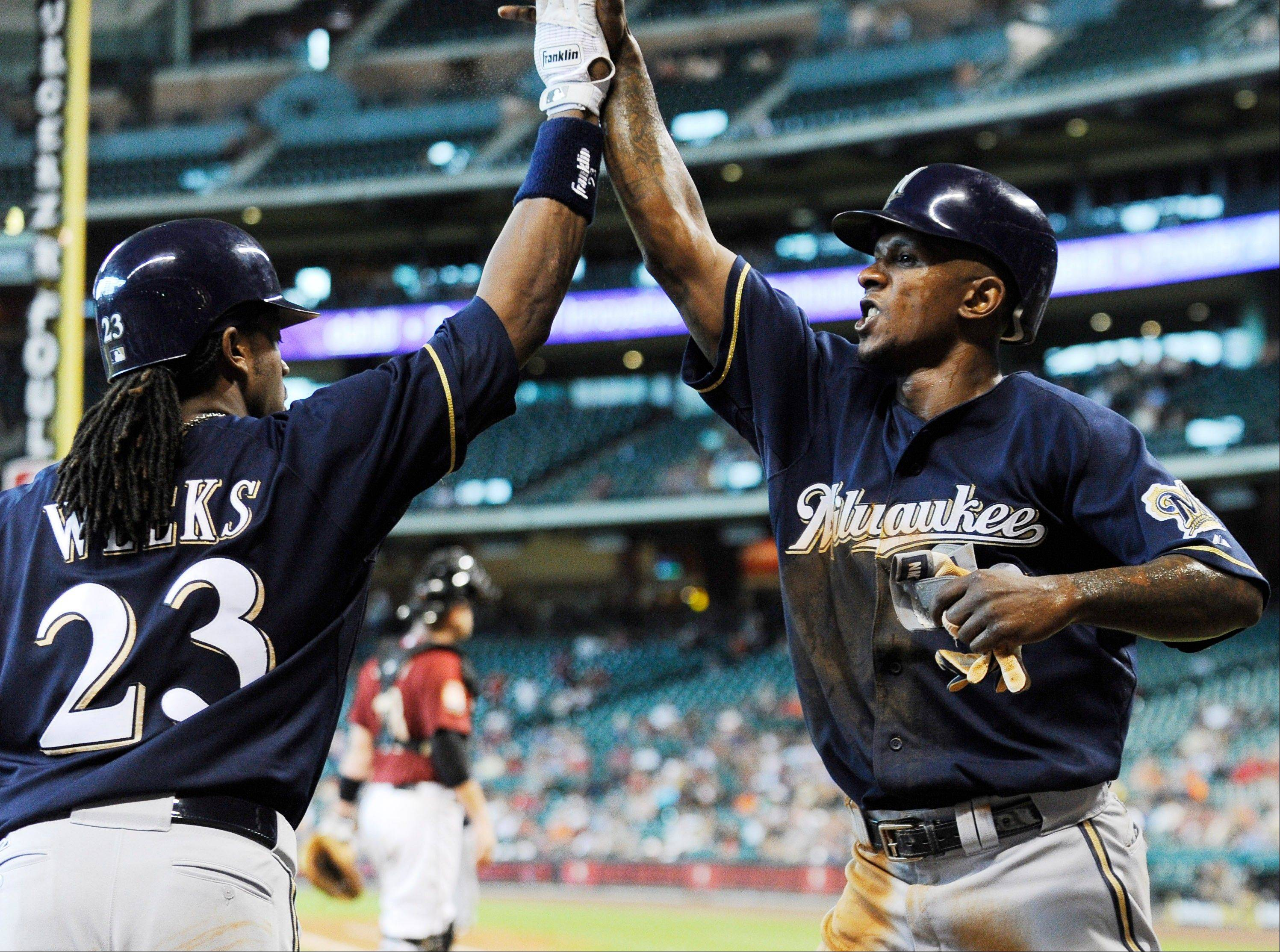 Milwaukee's Nyjer Morgan, right, is greeted by Rickie Weeks after scoring the go-ahead run on a bases-loaded single by Corey Hart in the 10th inning Sunday in Houston.