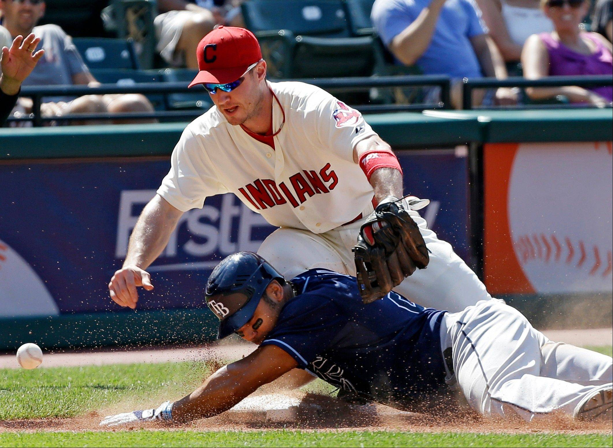 Tampa Bay's Carlos Pena slides into third with an RBI triple as the throw eludes Indians third baseman Jack Hannahan in the ninth inning Sunday in Cleveland.