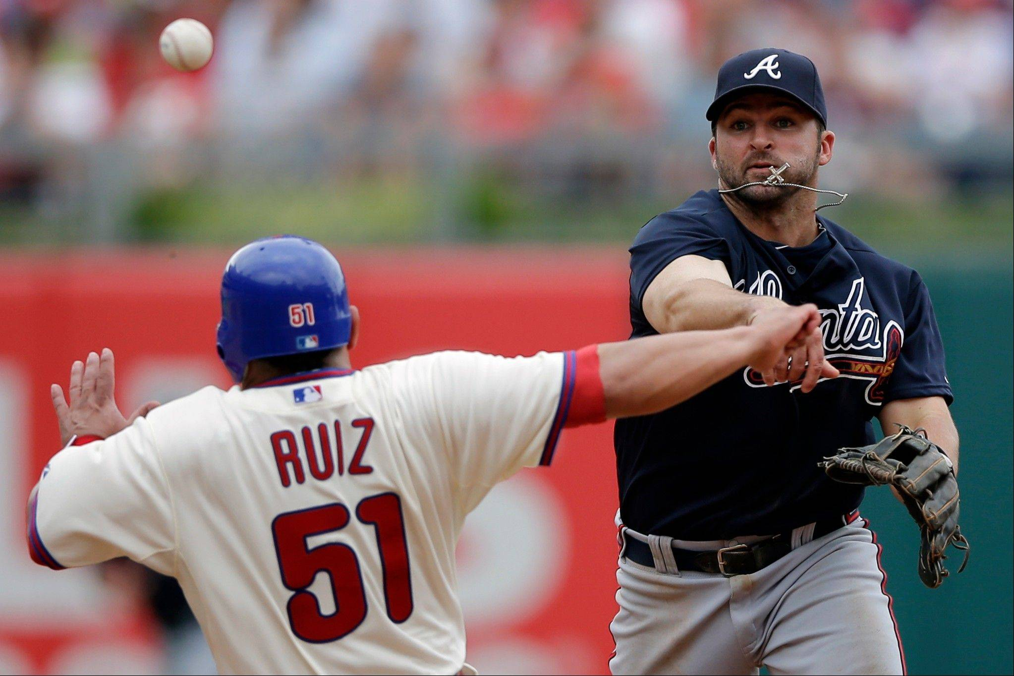 Atlanta second baseman Dan Uggla throws to first after forcing out the Phillies' Carlos Ruiz at second on a double play in the sixth inning Sunday in Philadelphia.