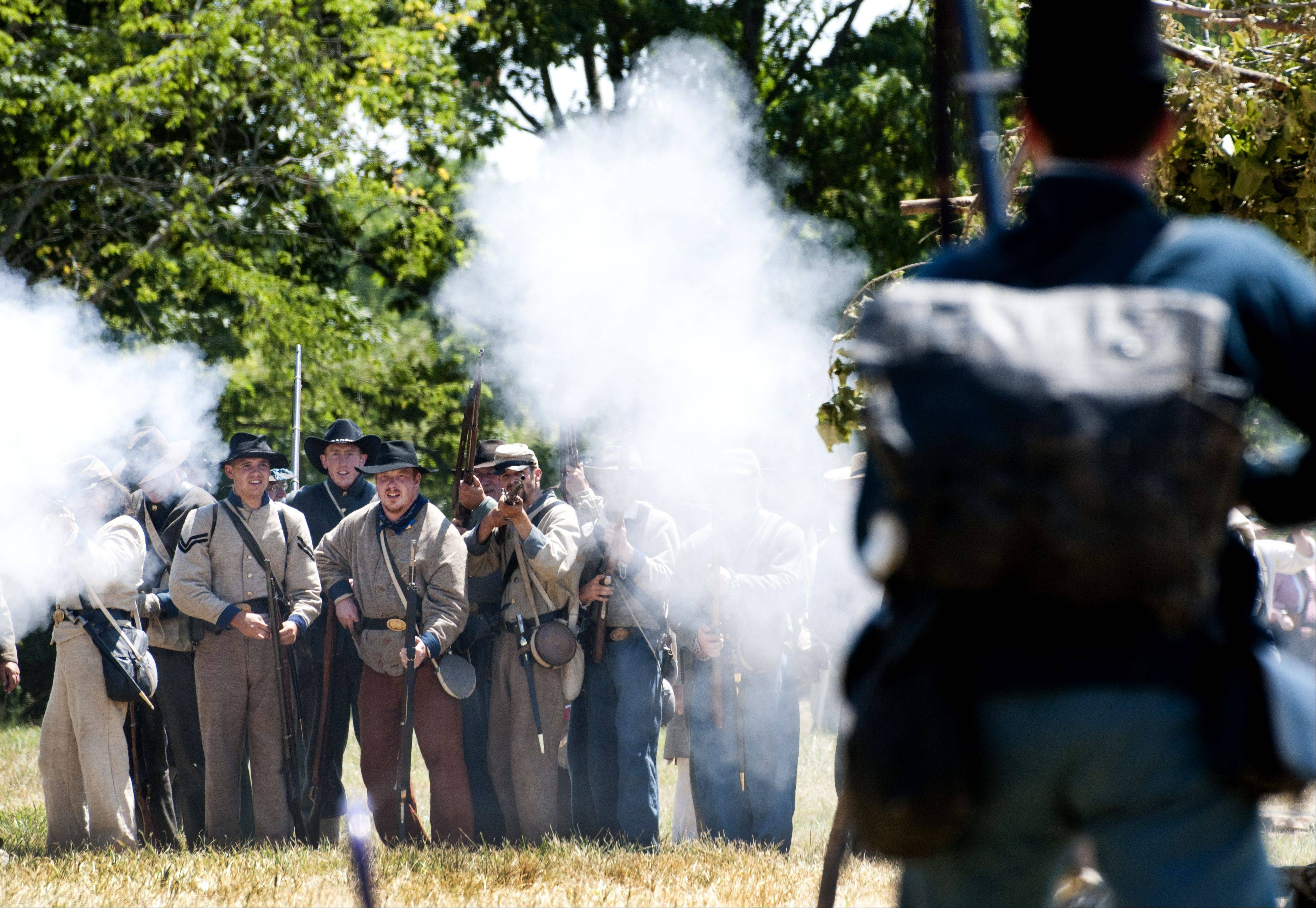 Confederate soldiers stage a counterattack against a Union flanking maneuver during Civil War Days Sunday in the Lakewood Forest Preserve near Wauconda.