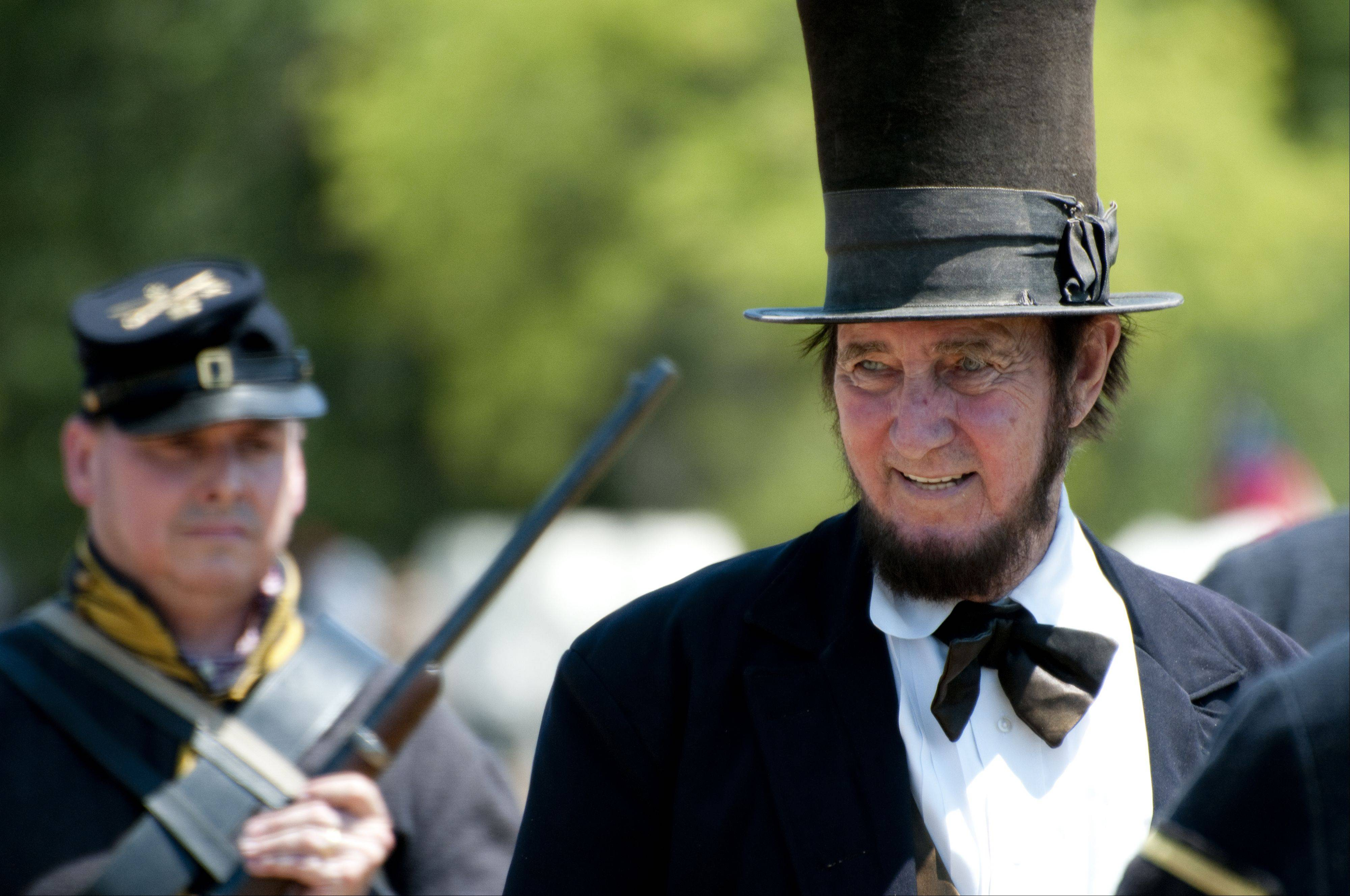 Abraham Lincoln smiles at the crowd as he makes his way to the battle re-enactment at the Civil War Days Sunday in the Lakewood Forest Preserve near Wauconda.