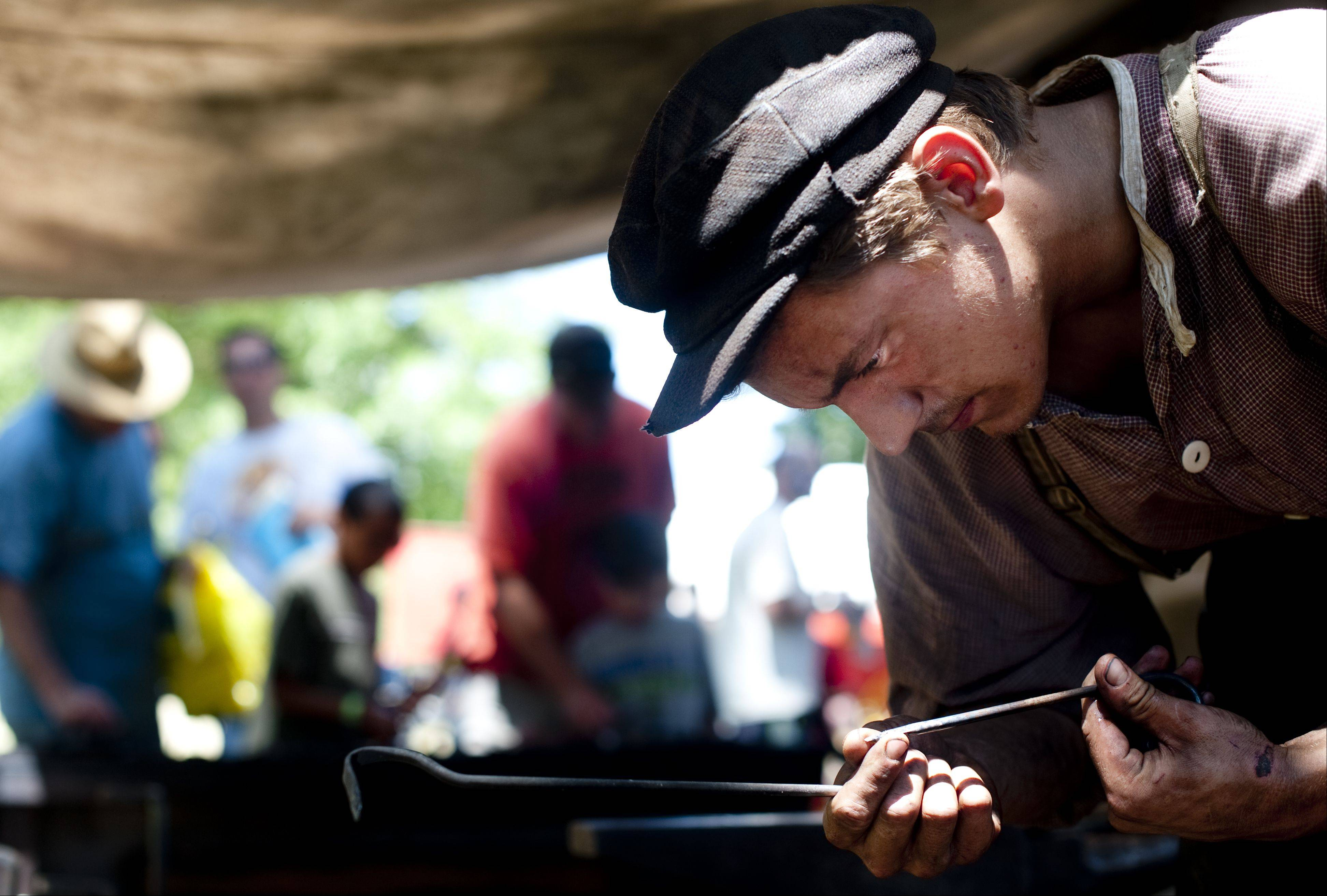 A Civil War era blacksmith works on a nail at Civil War Days Sunday in the Lakewood Forest Preserve near Wauconda. Visitors interacted with volunteers that explained the histories behind trades such as blacksmithing, sewing and medicine.