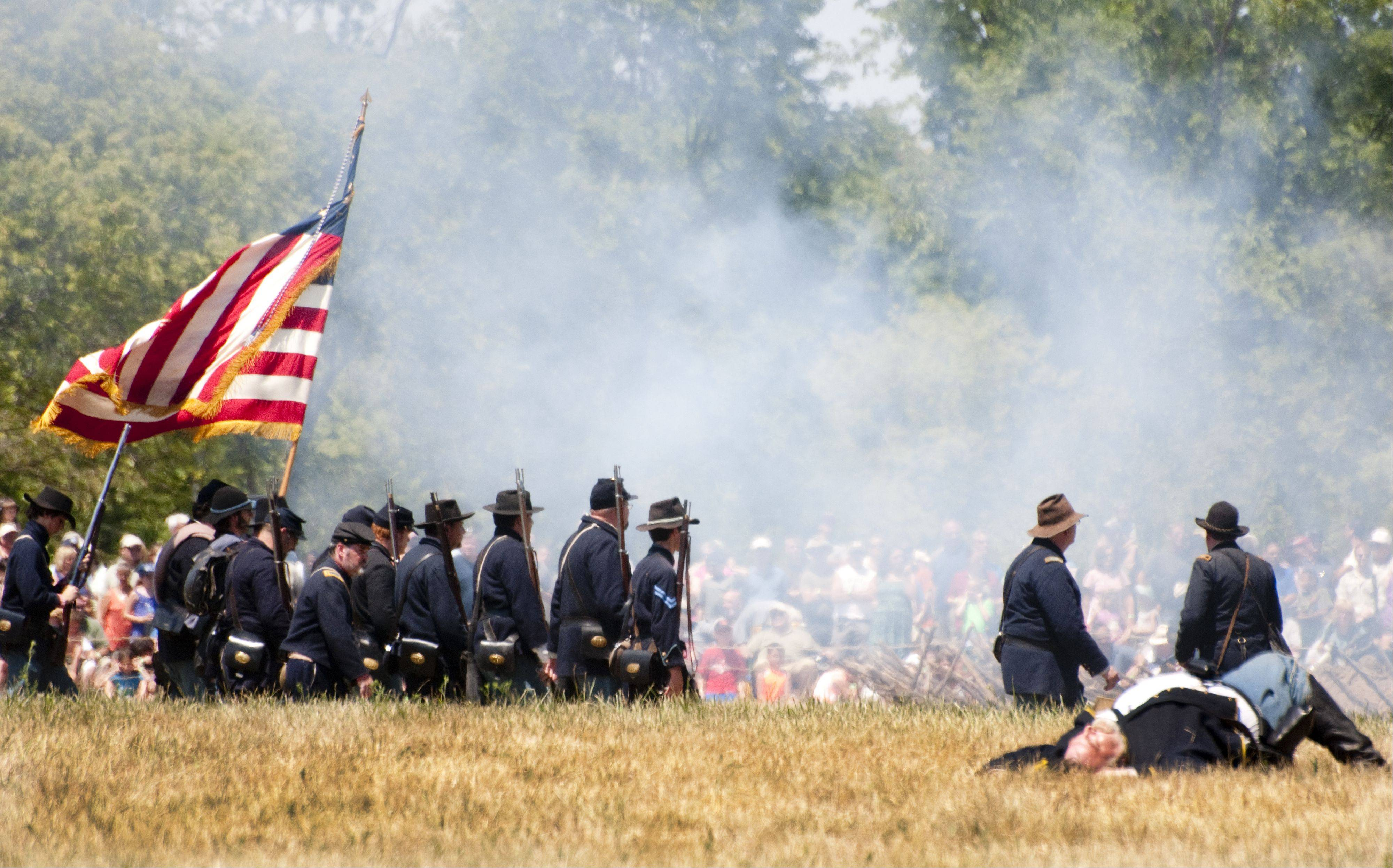 Union troops advance on the Confederates during a battle re-enactment as spectators observe Sunday during Civil War Days in the Lakewood Forest Preserve near Wauconda.