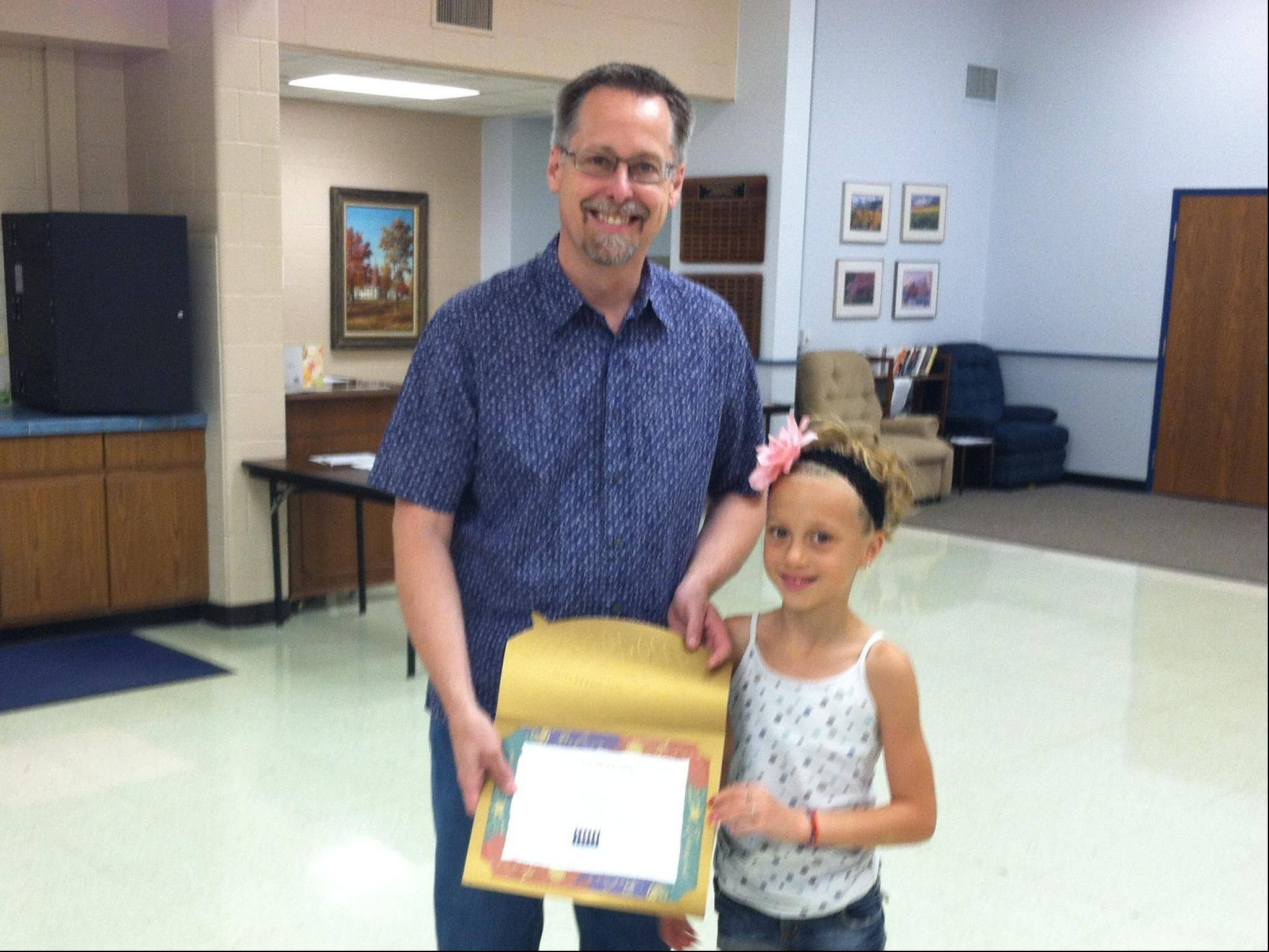 Izzy Ruiz, right, receives the Community Character Coalition�s Youth Service Award from coalition President Curt Hansen. Izzy, 7, won the award for organizing a lemonade stand to benefit Chicago Shriners Hospital.