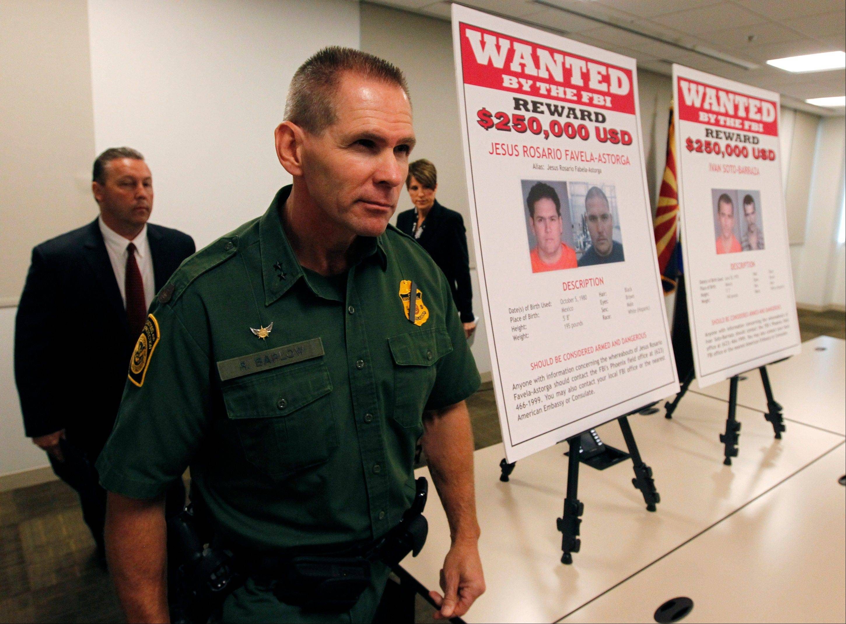 As they walk by wanted posters, Richard Barlow, front, Chief of the Tucson Sector of U.S. Customs and Border Protection Border Patrol, James L. Turgal, Jr., left, FBI Special Agent in Charge, and Laura E. Duffy, United States Attorney Southern District of California, leave a news briefing after it was announced that an indictment on five suspects related to the death of U.S. Border Patrol agent Brian Terry Monday.