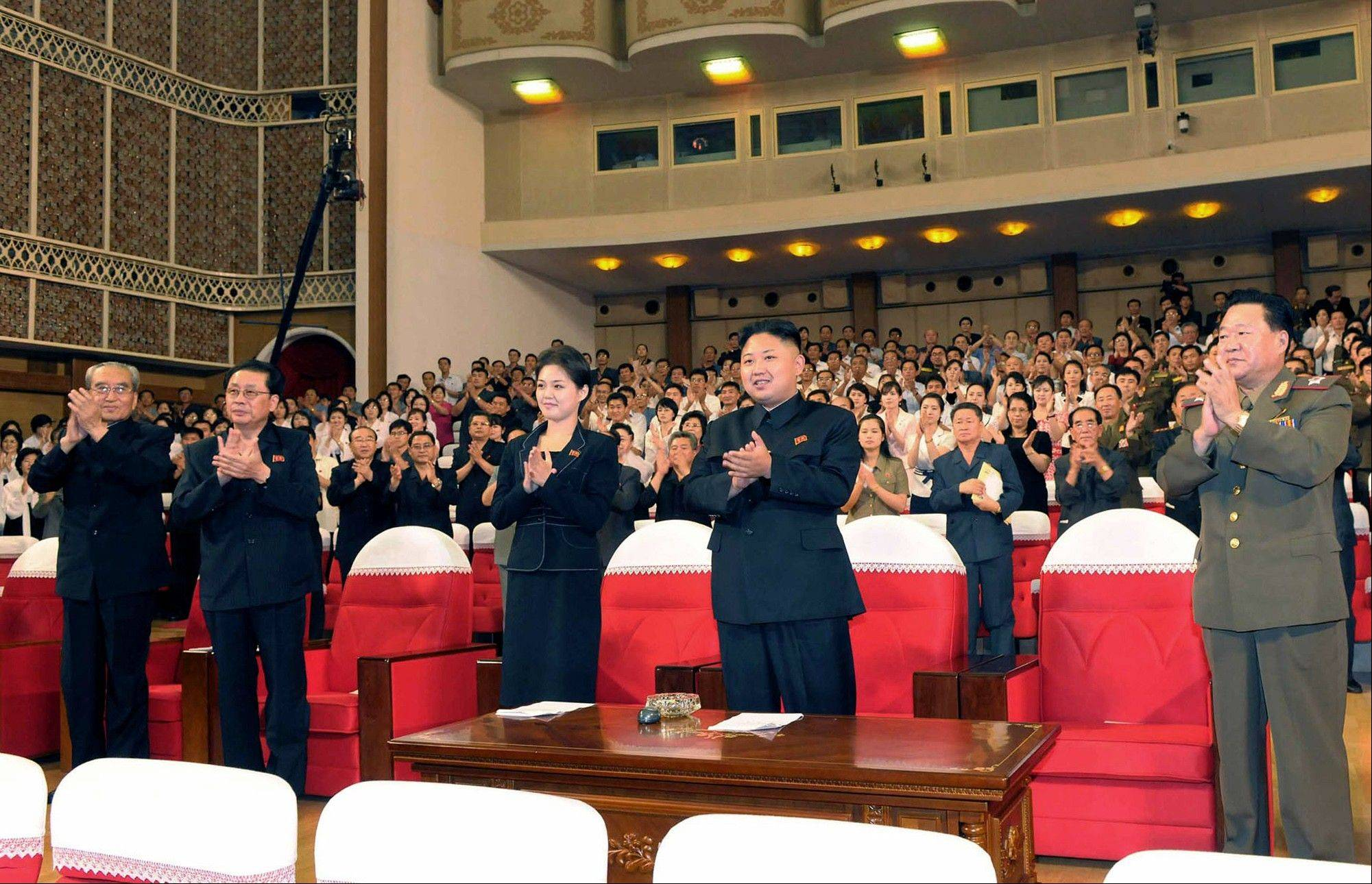North Korean leader Kim Jong Un, center right, and a woman applaud with others as they watch a performance by North Korea�s new Moranbong band in Pyongyang Friday. The source did not identify the woman but South Korean media speculated she could be Kim�s younger sister or wife.