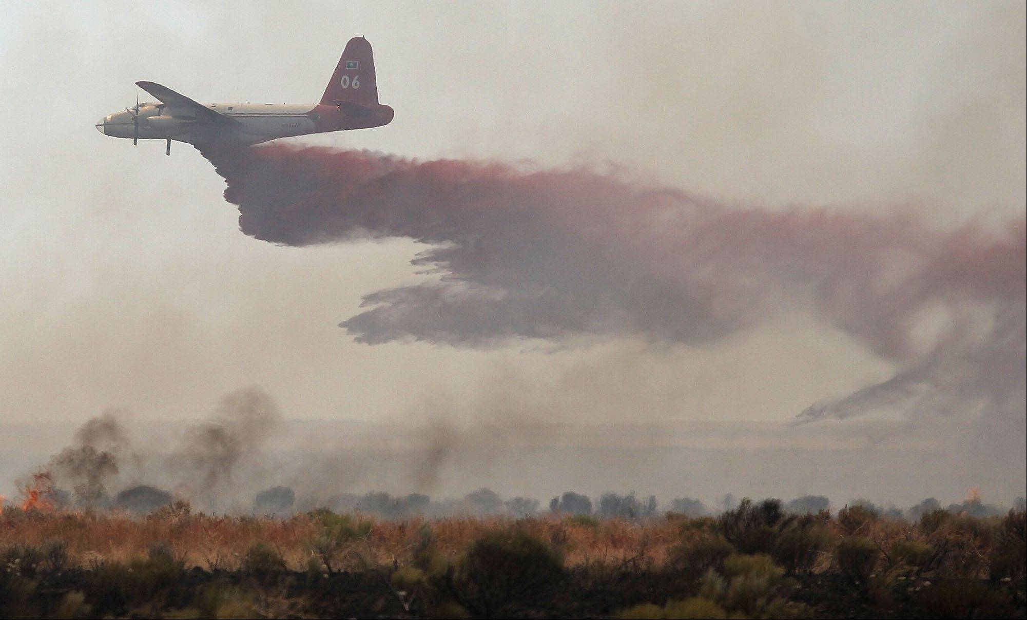 An aircraft drops fire retardant on the Kinyon Road Fire off of Horse Butte Road west of Castleford, Idaho on Sunday. More than 150 firefighters are fighting the blaze that has consumed over 75,000 acres.