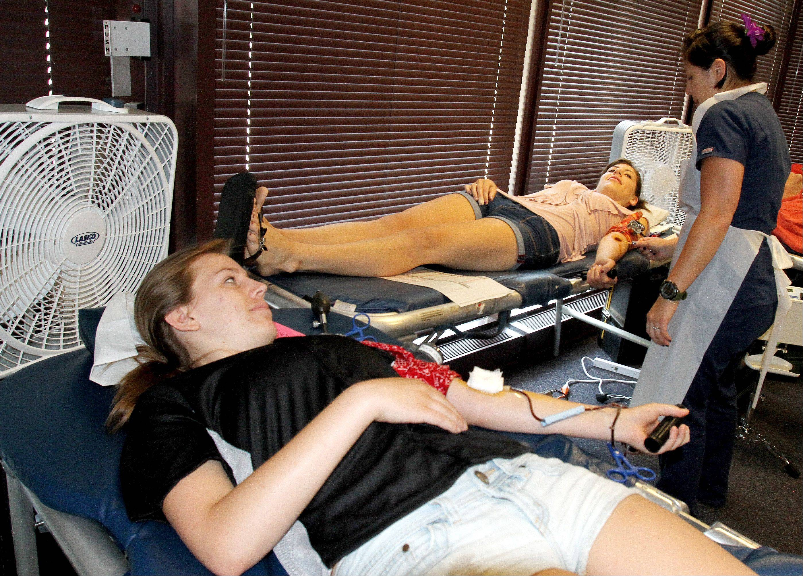 Danielle Kochurka and Kristen Rafferty donate blood during a drive at Naperville city hall. Tending to them is Kat Corono, phlebotomist at Heartland Blood Centers.