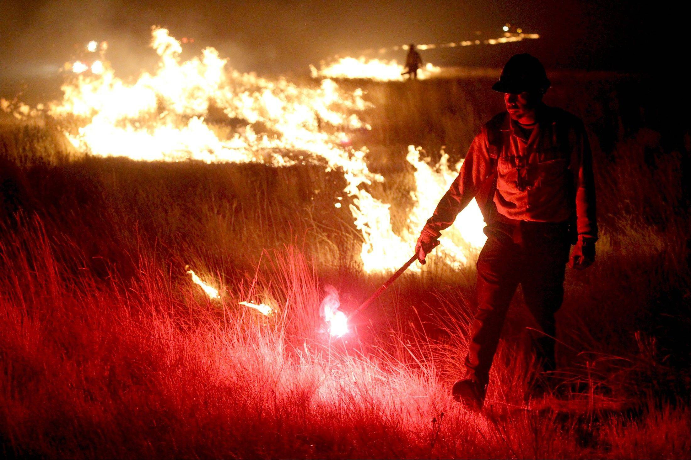 Shawn Torres, of the U.S. Bureau of Land Management, starts a backburn while battling the Kinyon Road Fire west of Castleford, Idaho, on Saturday. More than 150 firefighters are fighting the blaze that has consumed more than 75,000 acres.