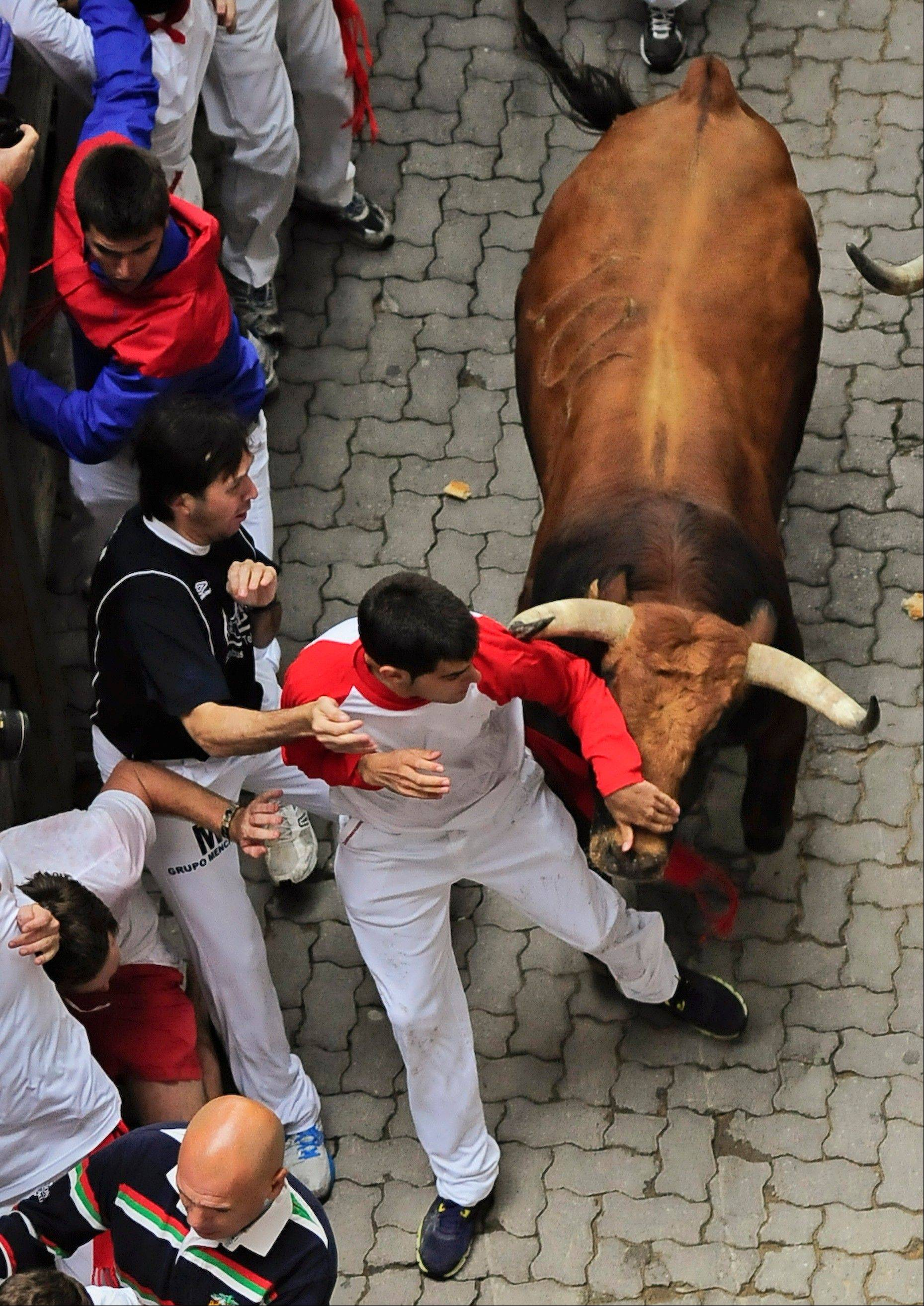 Reveler runs on the Callejon way beside a Cebada Gago ranch fighting bull during the third day of the running of the bulls at the San Fermin fiestas in Pamplona, Spain, on Monday.