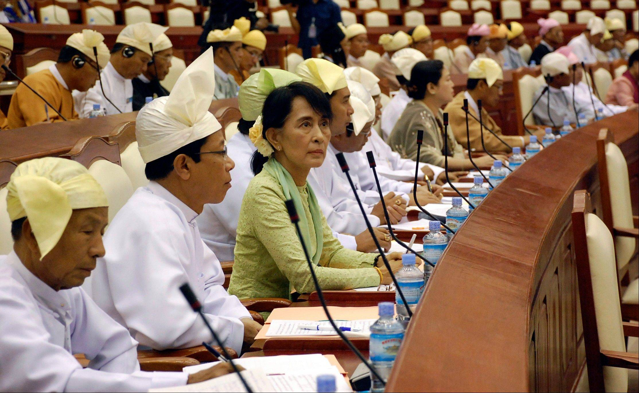 Myanmar opposition leader Aung San Suu Kyi, third from left, takes a seat for a regular session of Parliament at Myanmar�s Lower House for the first time Monday.