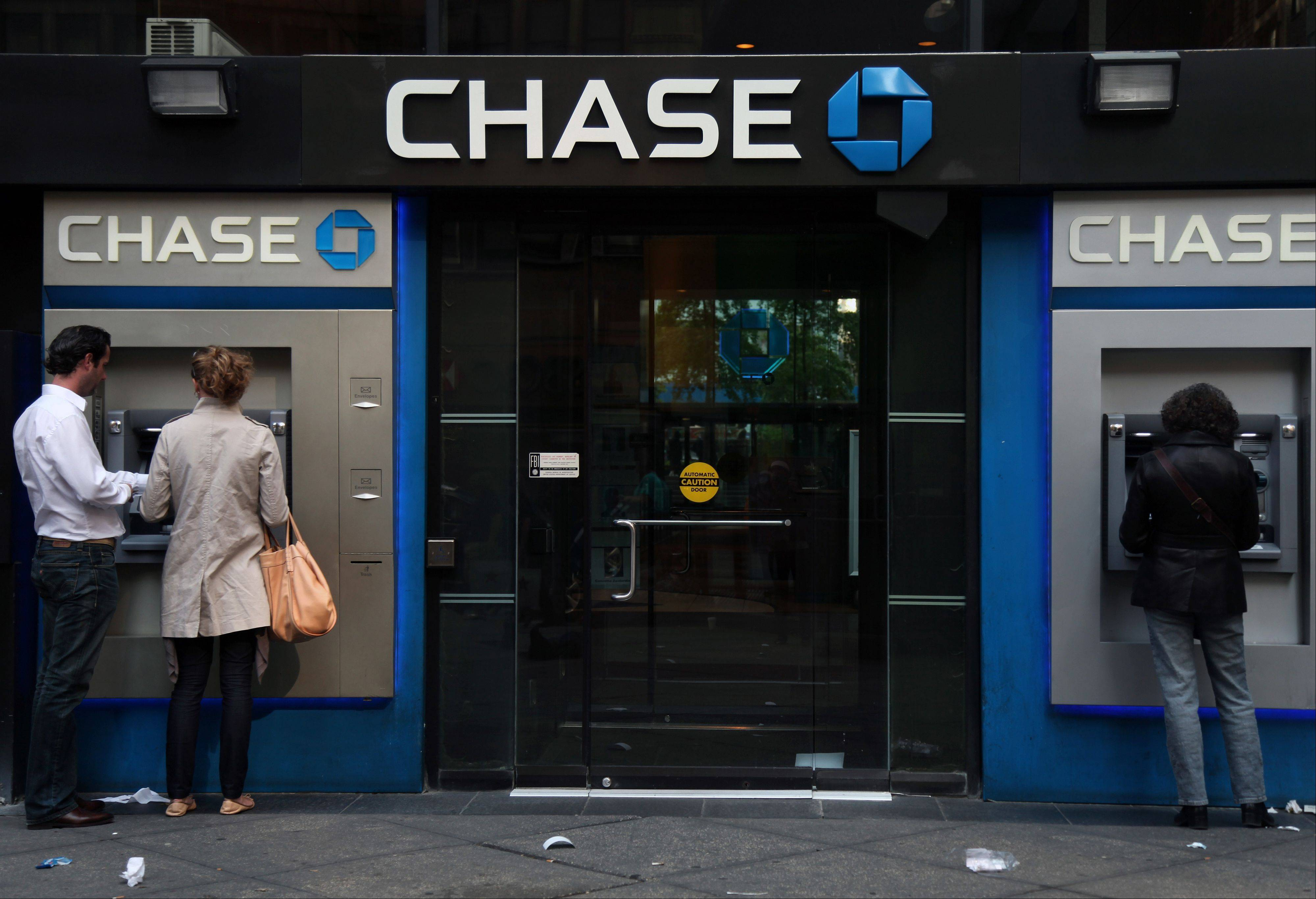 People use Chase ATM machines at a branch in New York. Americans stepped up their borrowing in May, helped by the largest one-month gain in credit card debt in more than four years. But overall credit card use is still well below where it was just before the Great Recession began.