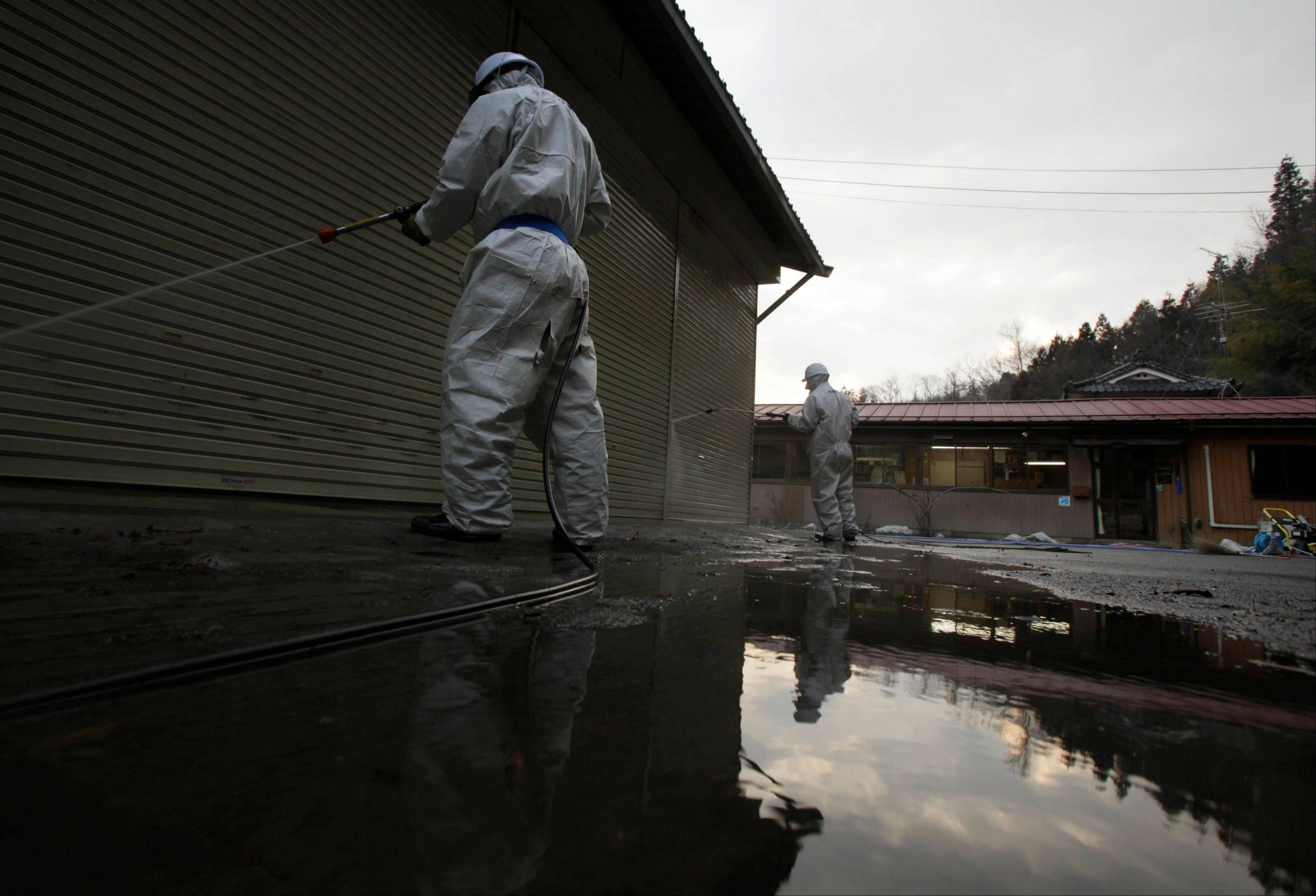 Workers spray the walls of a radiation-contaminated warehouse in Fukushima, northeastern Japan.