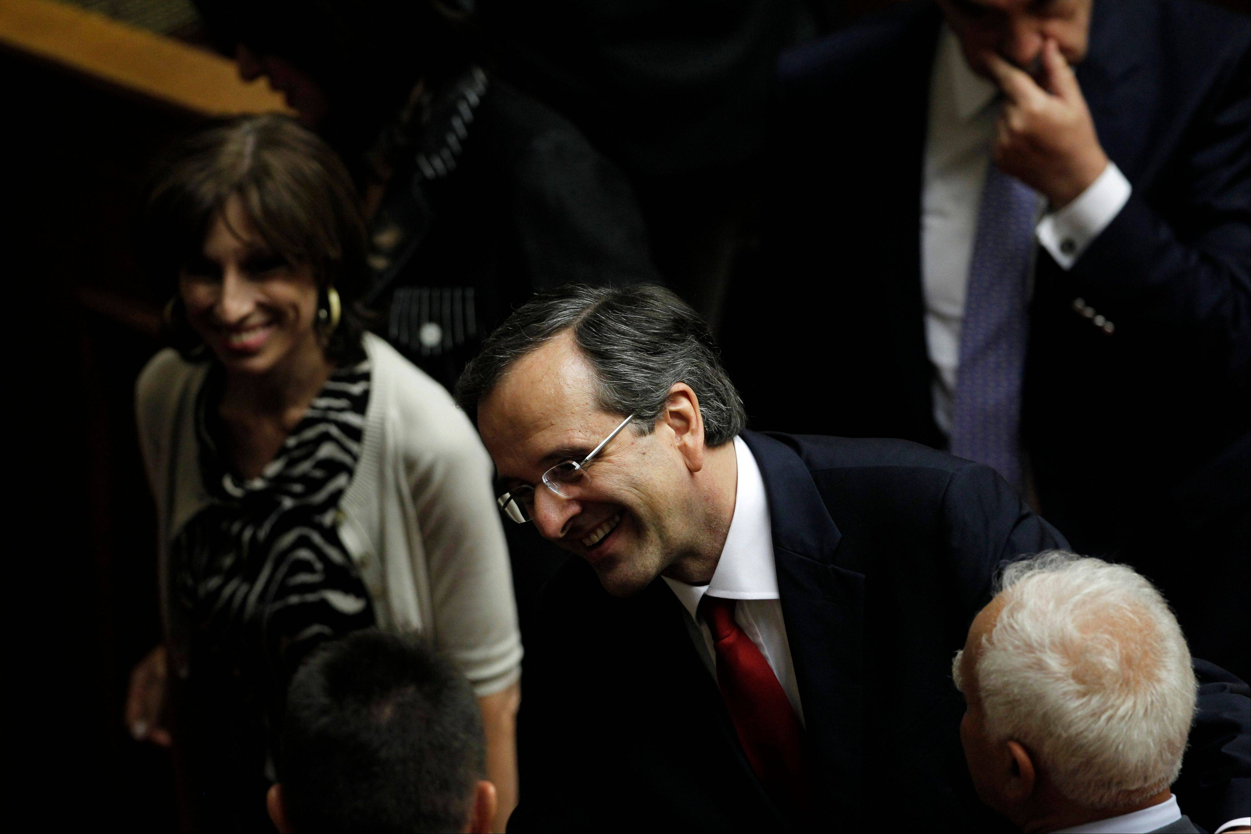 Greek Prime Minister Antonis Samaras is congratulated by lawmakers at Parliament after winning a vote of confidence in Athens, Greece, late Sunday.