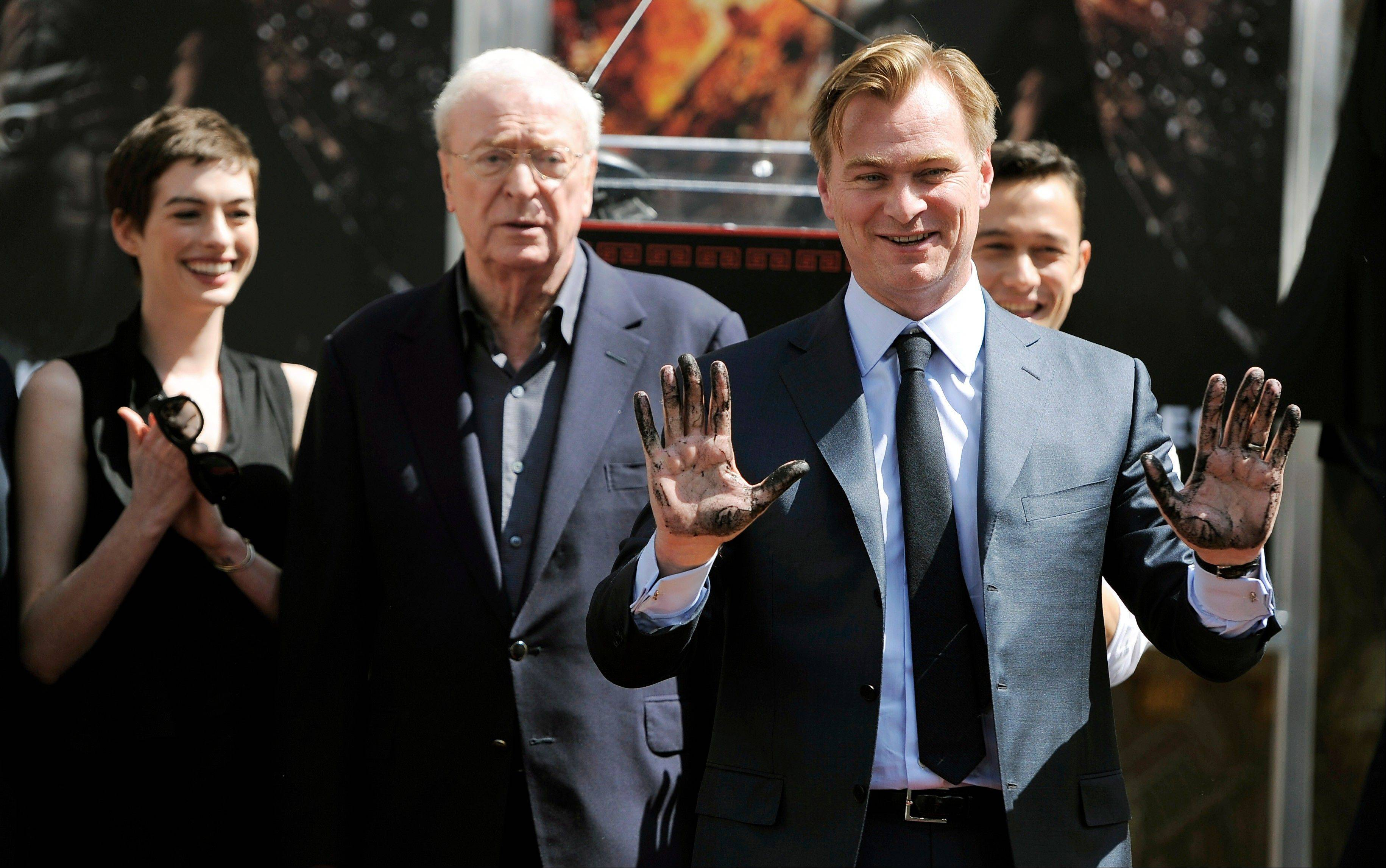"Christopher Nolan, director of the upcoming film ""The Dark Knight Rises,"" holds up his hands after putting them in cement during a ceremony for him at Grauman's Chinese Theatre. Looking on from left are cast members Anne Hathaway, Michael Caine and Joseph Gordon-Levitt."