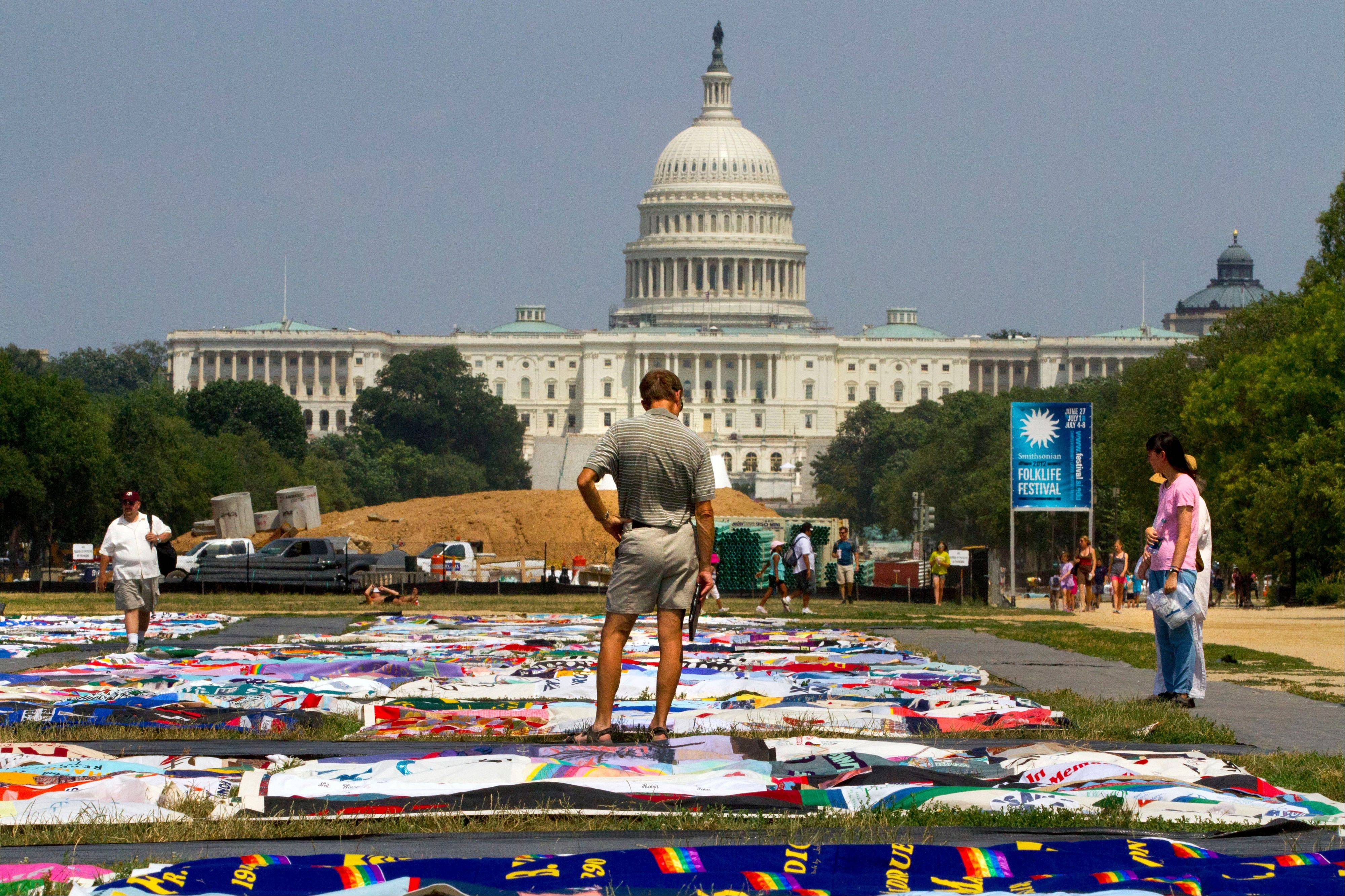People visit the AIDS Memorial Quilt on display as part of the Smithsonian Folklife Festival on the National Mall in Washington. More than 20,000 international HIV researchers and activists will gather in the nation's capital later this month.