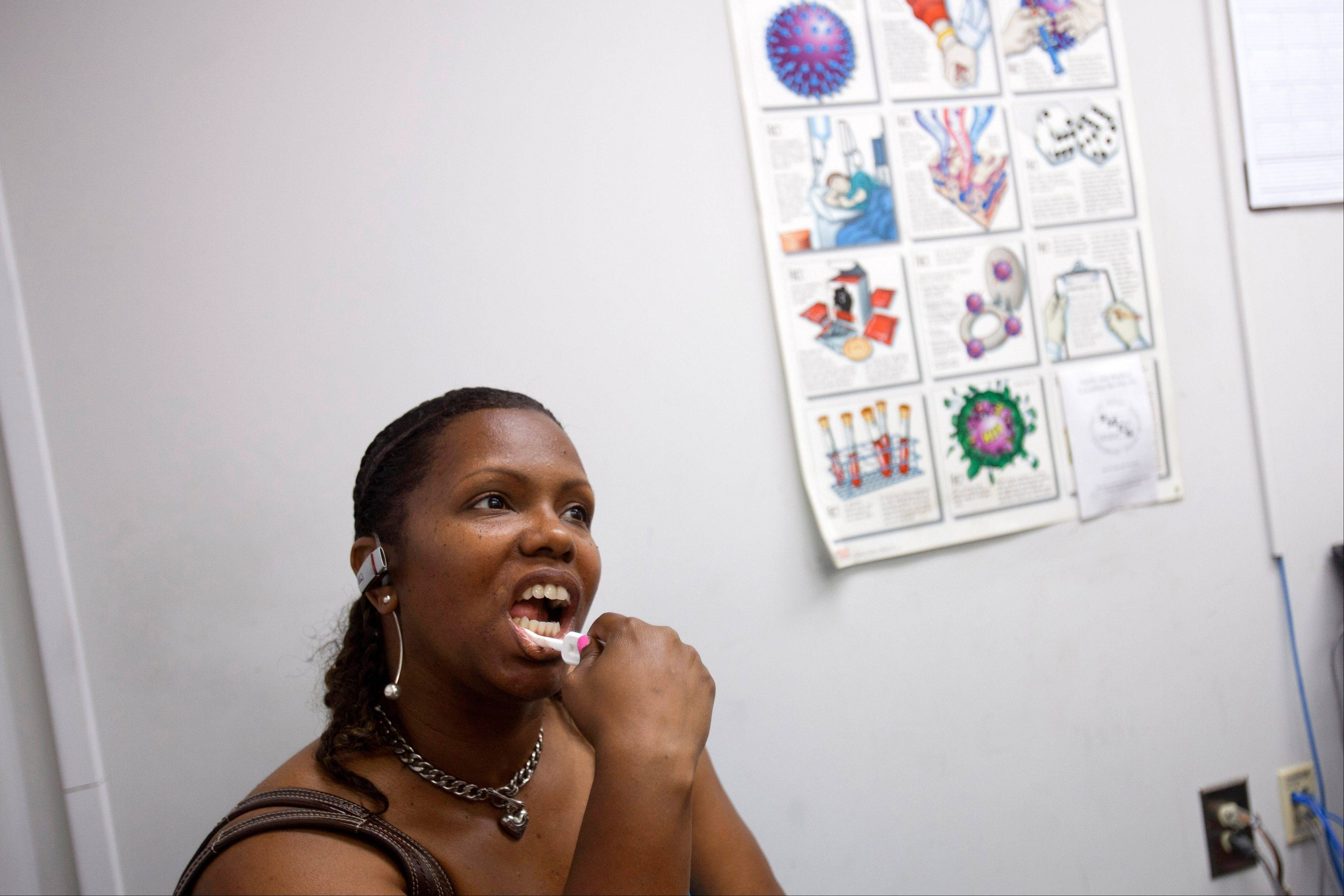 Robin Reese, 41, of Washington, D.C., uses an oral test for HIV, in front of a poster detailing facts about HIV/AIDS, inside the HIV Testing Room at the Penn Branch of the District of Columbia Department of Motor Vehicles.