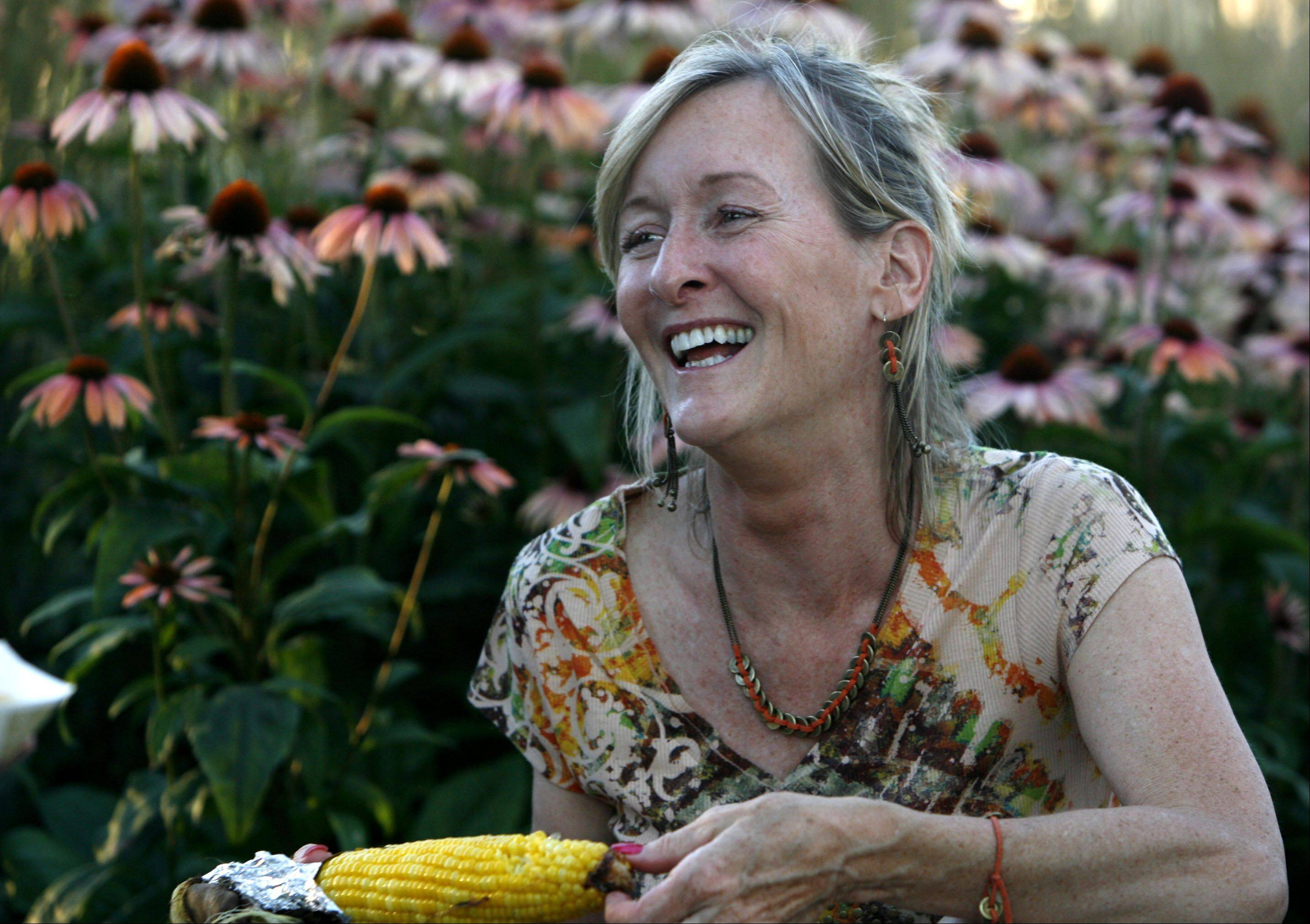 GEORGE LECLAIRE/gleclaire@dailyherald.com Donna Carmody of Mt. Prospect enjoys a laugh with a friend as she eats grilled corn while sitting in front of a bed of flowers at the Taste of Lincolnshire 2010.