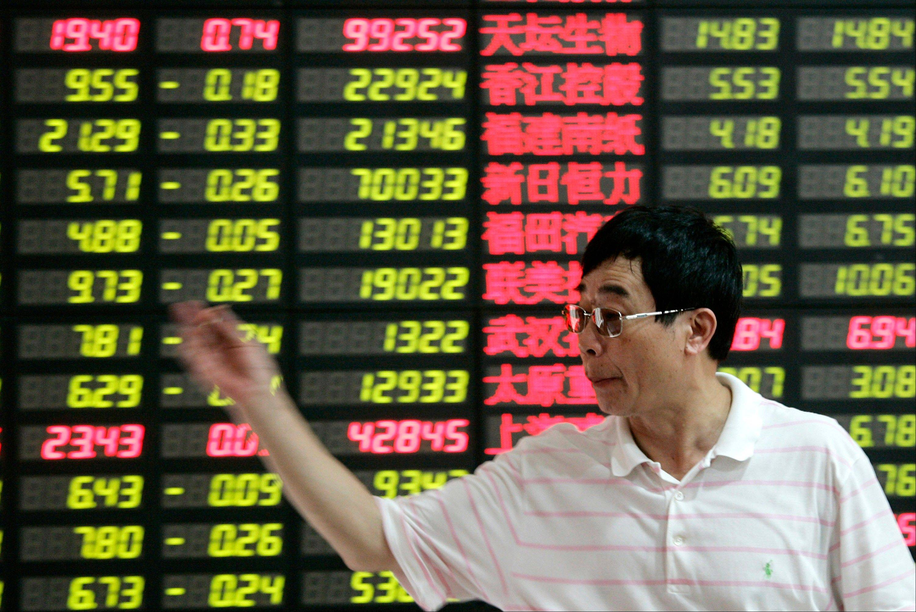 An investor gestures in front of the stock price monitor at a private securities company Monday .
