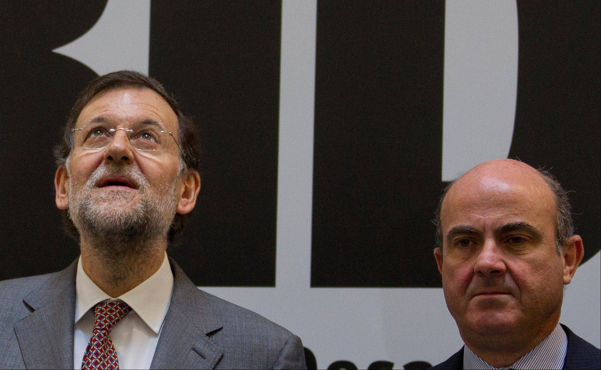 Spain's Prime Minister Mariano Rajoy, left, and Economy Minister Luis de Guindos pose during the official opening of the new headquarters of the Inter-American Development Bank in Madrid.