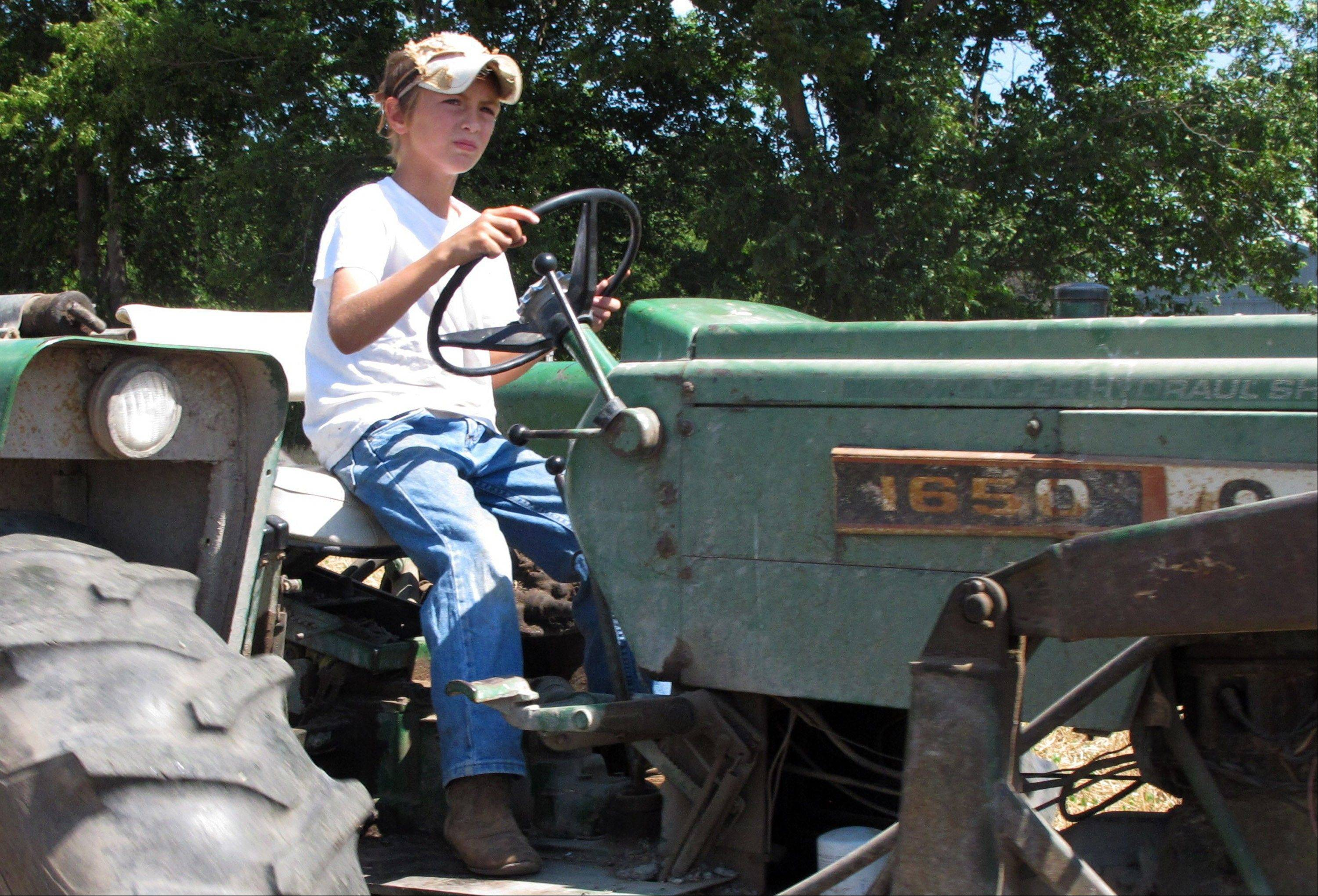 Ten-year-old Jacob Mosbacher guides a tractor through a bean field on his grandparents' property near Fults, Ill.