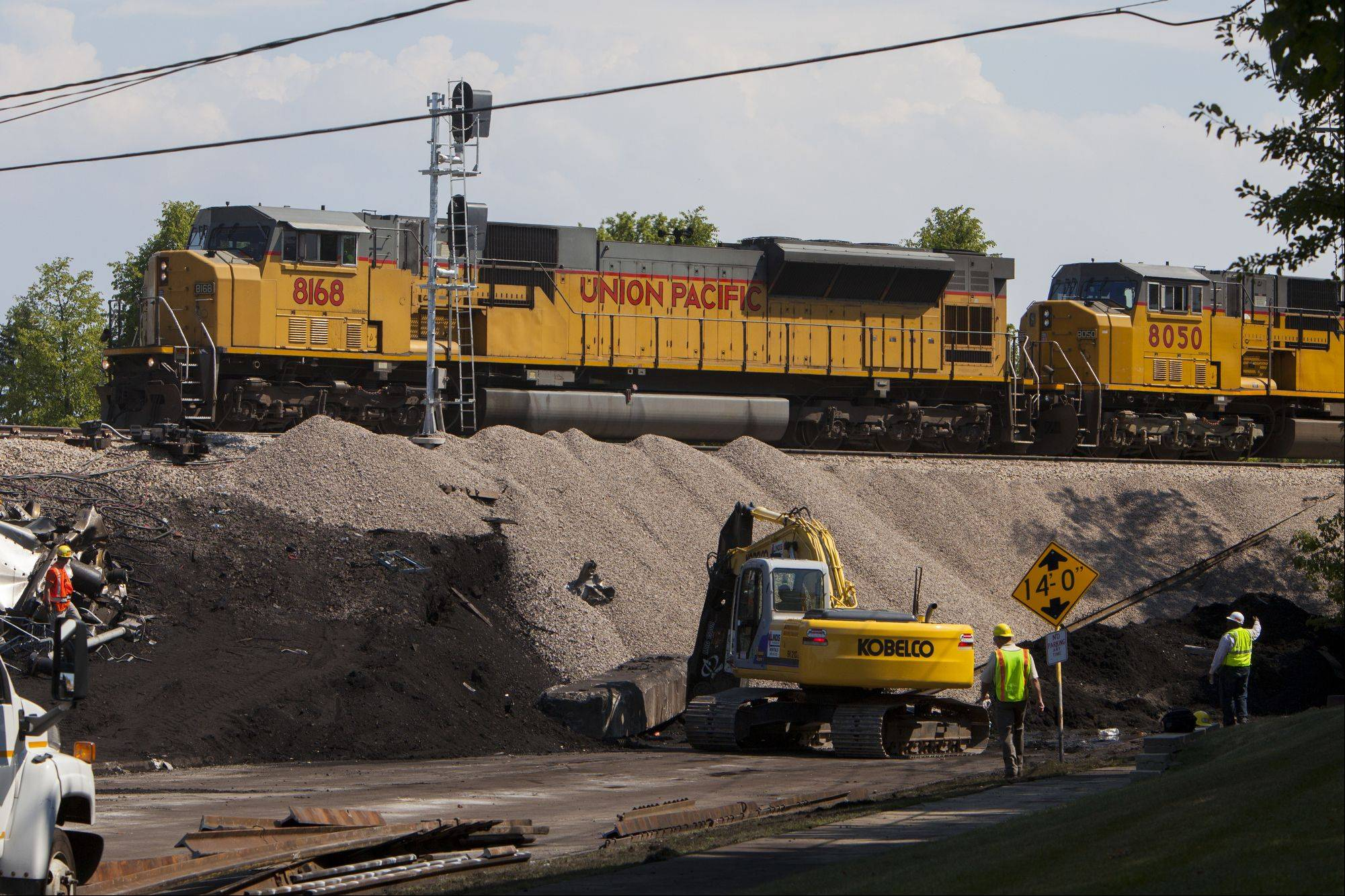 Union Pacific workers clean up debris Monday from the July 4 bridge collapse.