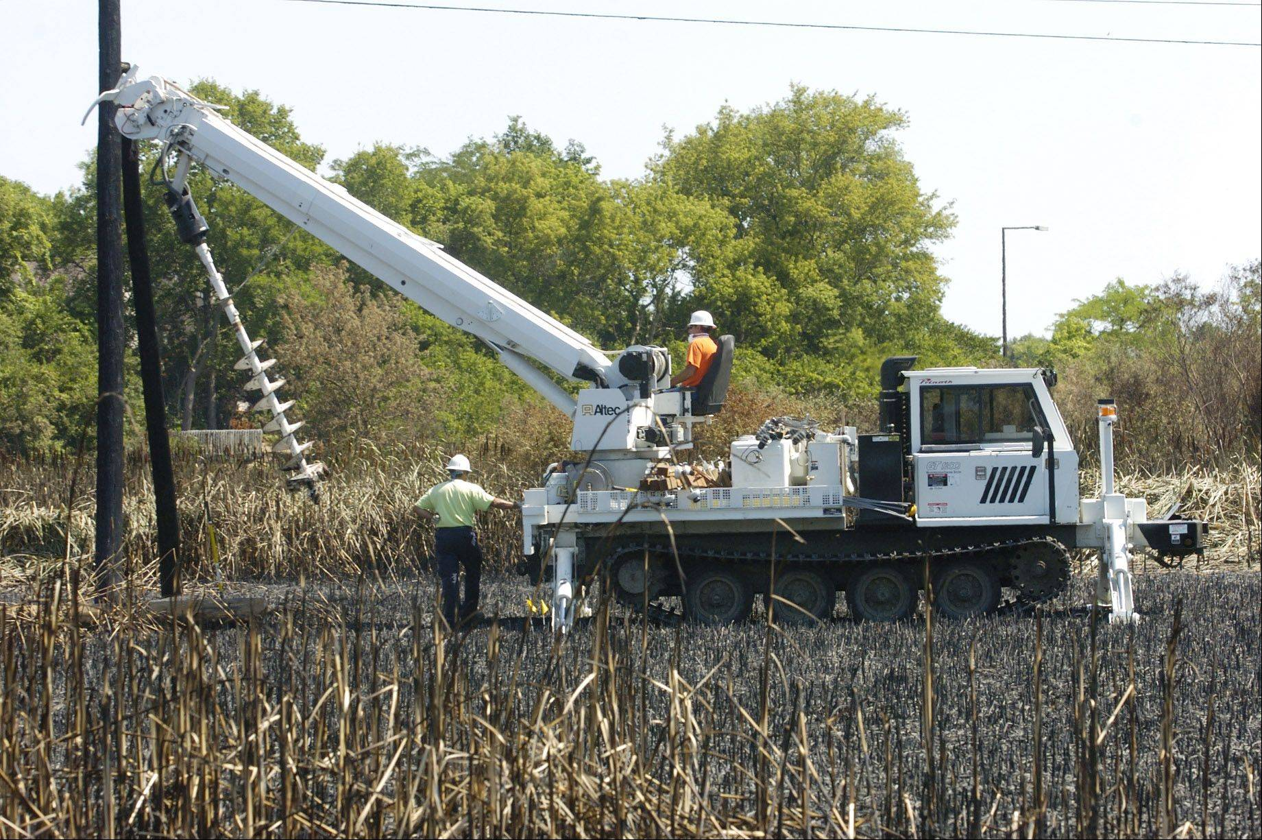 ComEd crews replace utility poles damaged in the Buffalo Grove brush fire.