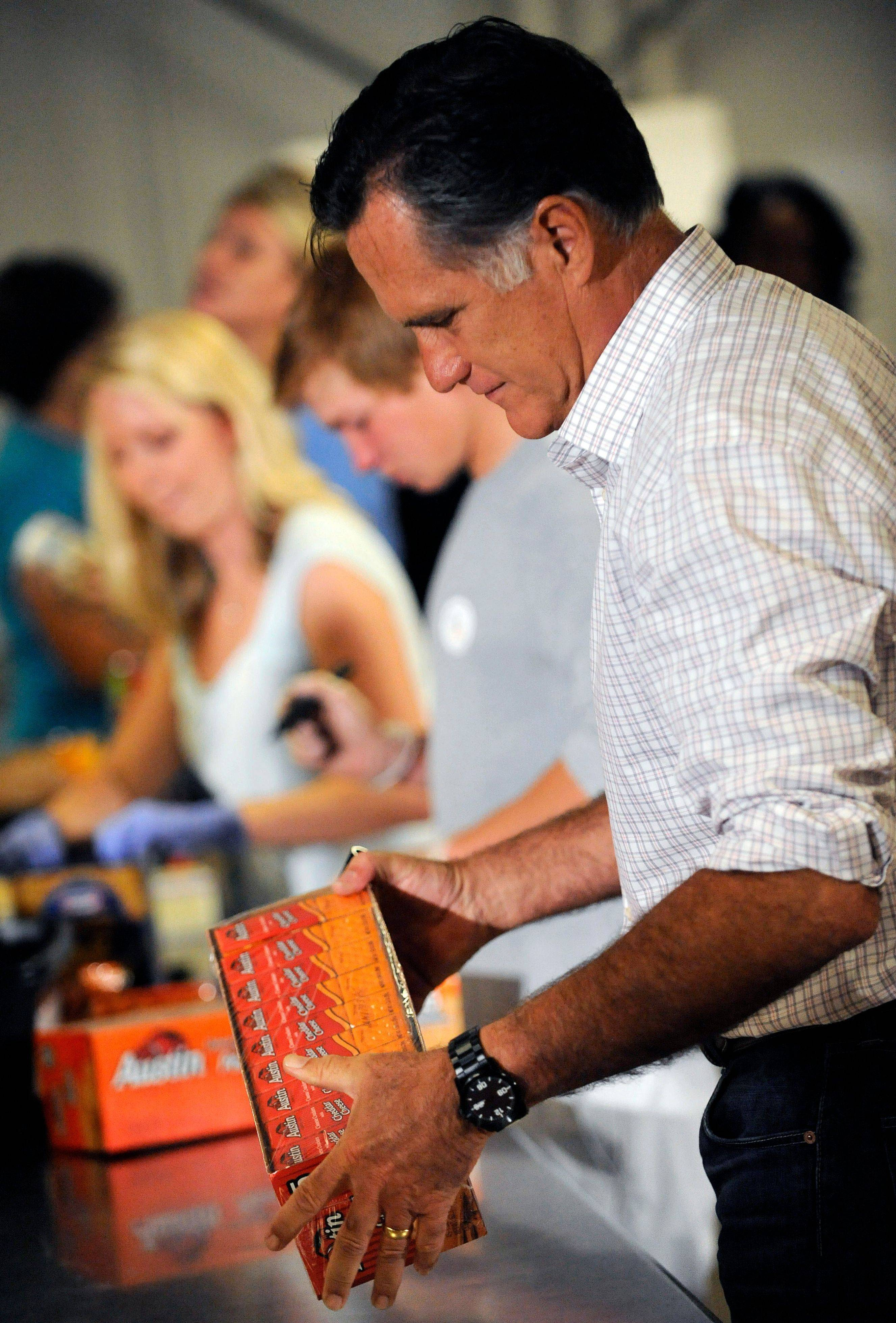 Republican presidential candidate Mitt Romney works alongside volunteers at Care and Share during his visit to Colorado Springs, Colo., on Tuesday. He helped box food for firefighters and people displaced by the fires that have plagued the state this summer.