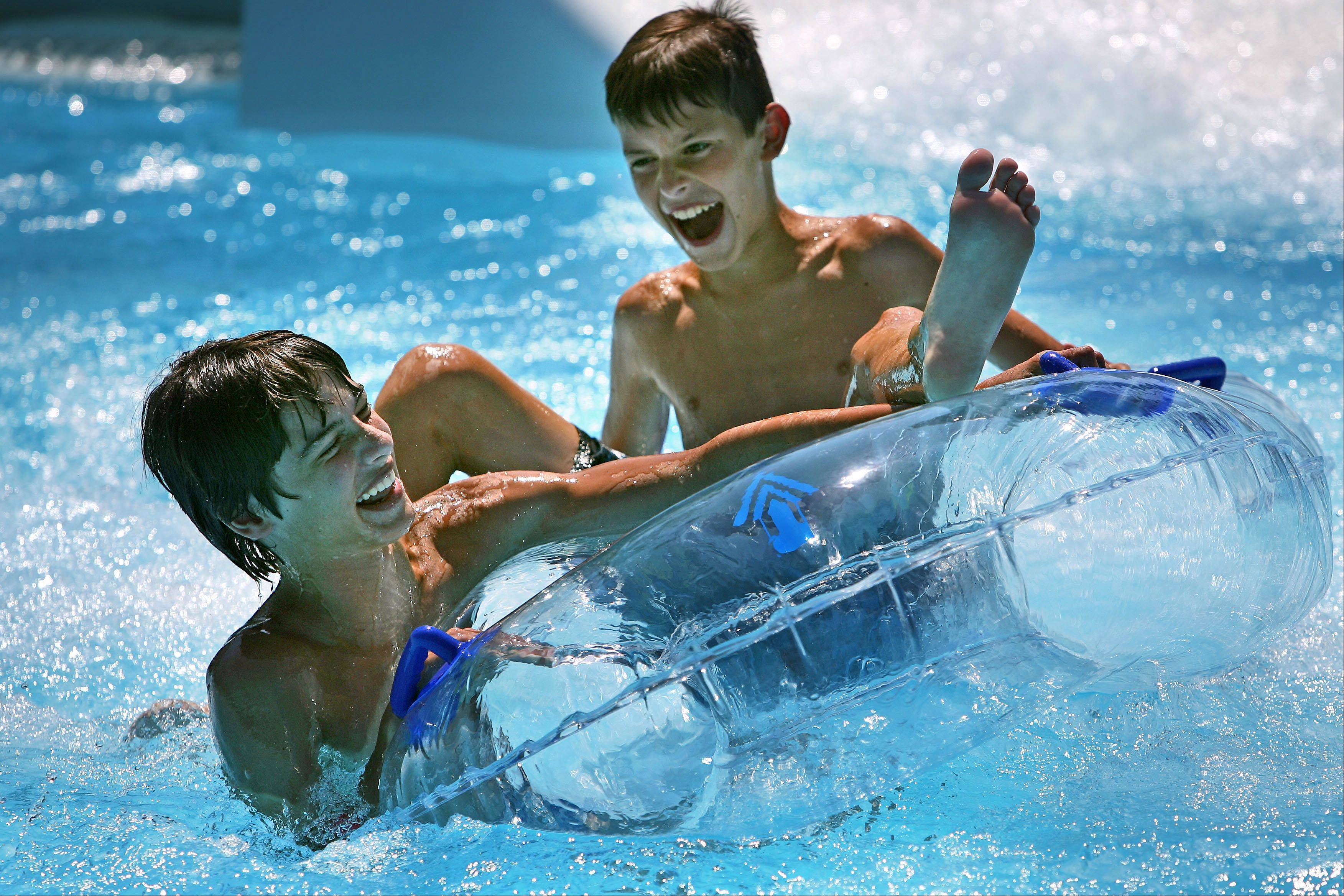 Andre Hromic of Wauconda, left, and Alex Gracanin of Chicago, both 12, splash into the water after going down a slide Tuesday at Barefoot Bay Family Aquatic Center in Mundelein.