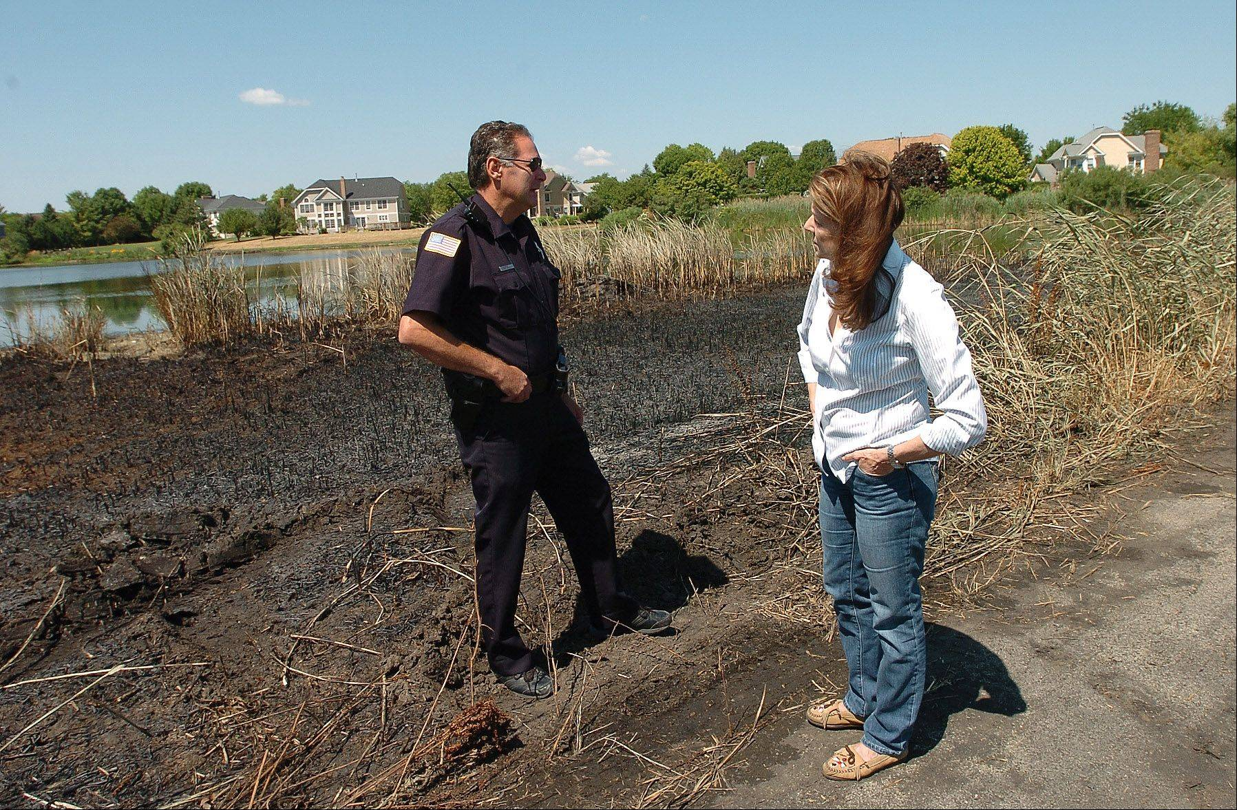 Susan Zerin talks with a Buffalo Grove police officer who was on the scene Sunday for the Buffalo Grove brush fire.