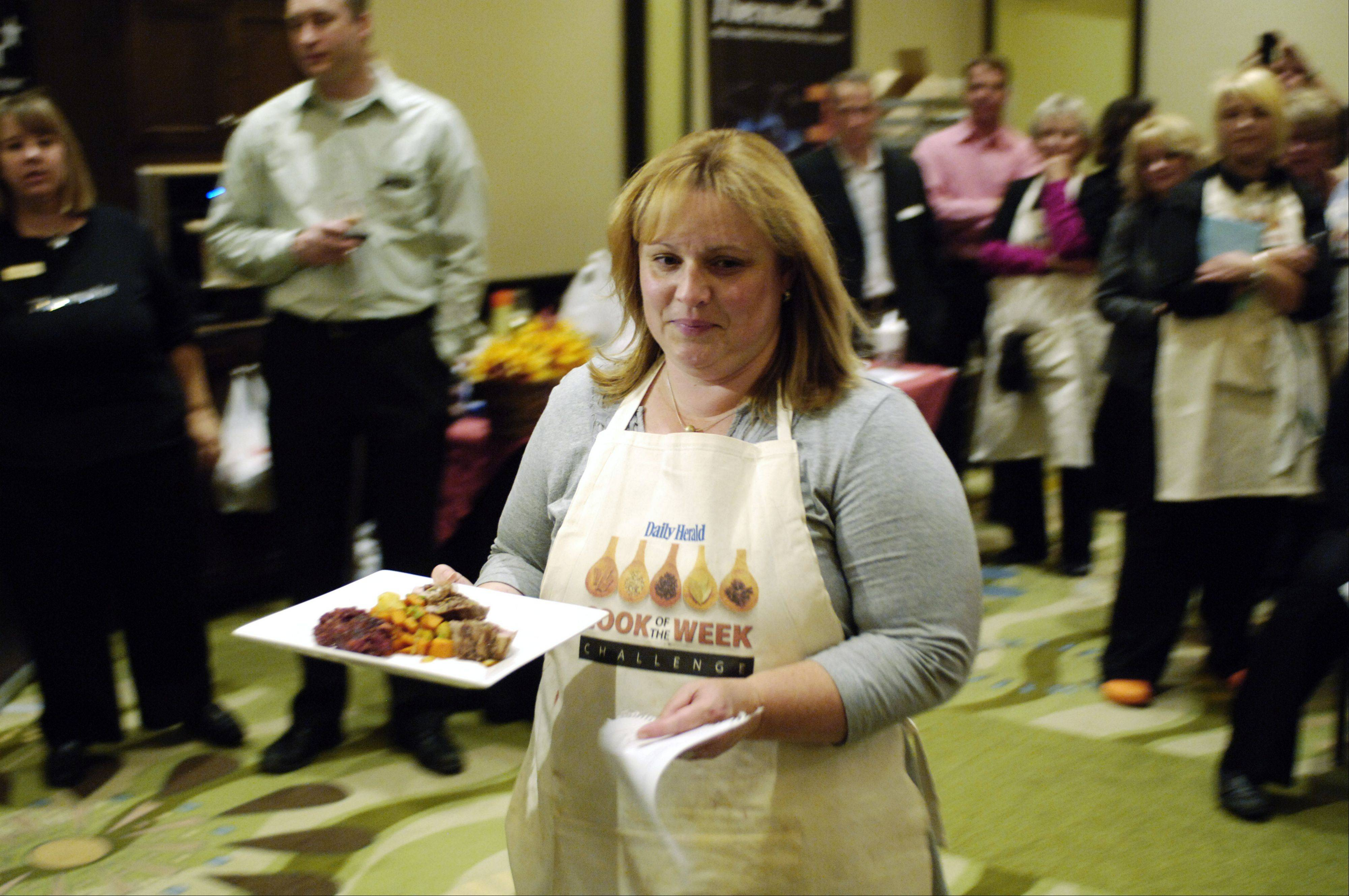 Penny Kazmier carries her pork creation to the judge's table during the Daily Herald Cook of the Week Challenge live cook-off.