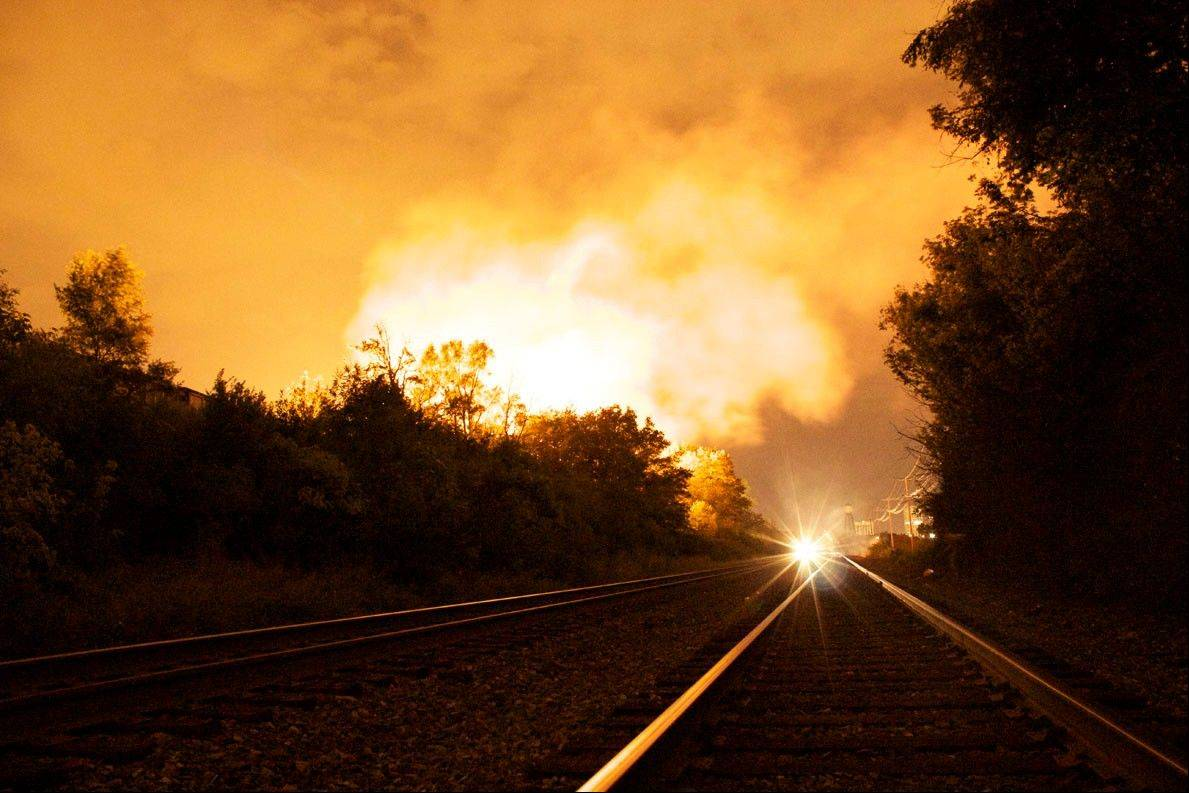 People watch the flames shoot up from a freight train that derailed early Wednesday morning July 11, 2012, in Columbus Ohio. Lt. Terry Bush says the accident happened at about 2 a.m. Wednesday in a mixed-use part of the city, and people living in one-mile radius of the blast have been evacuated.