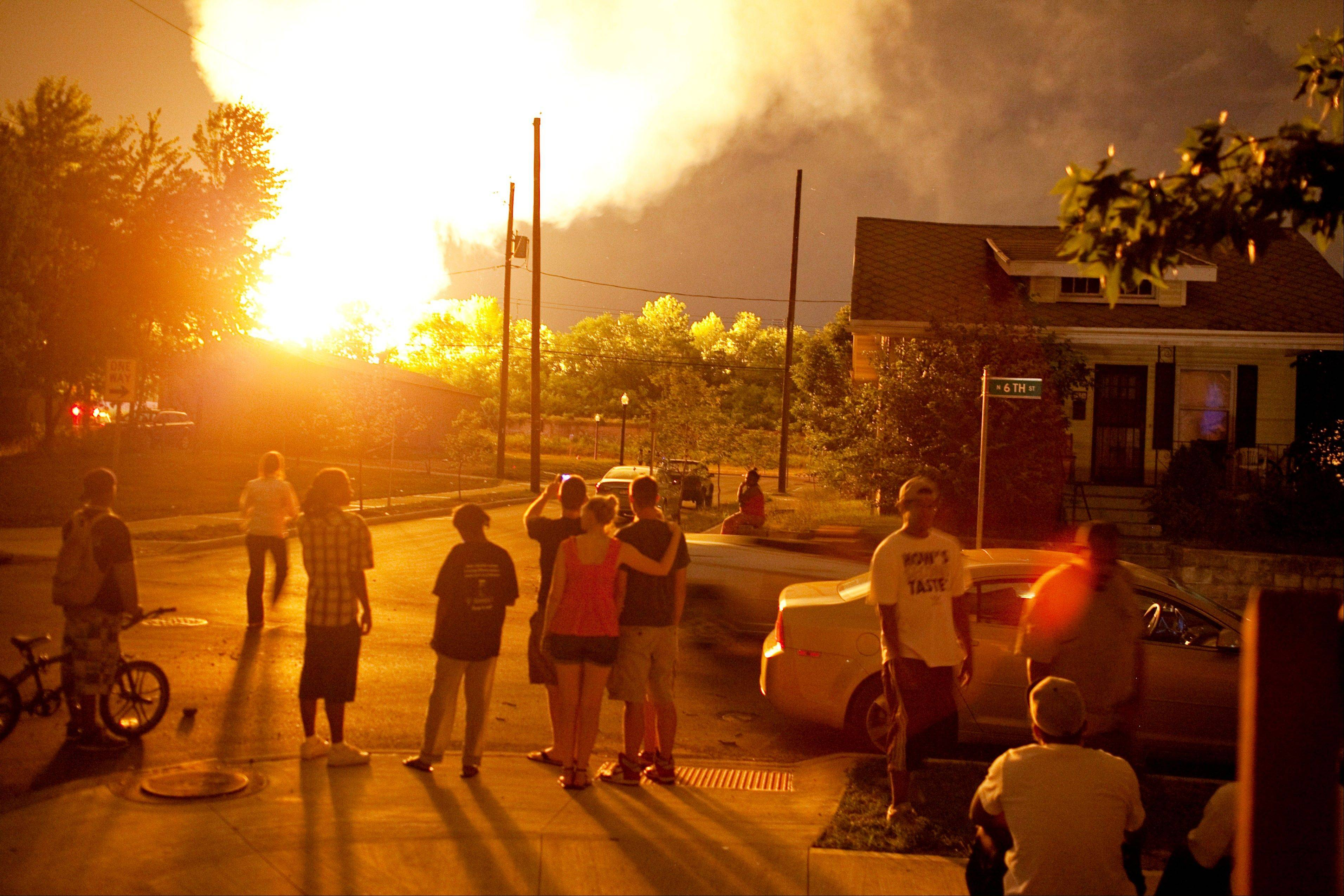 Flames rise from a derailed freight train, left unseen, early Wednesday July 11, 2012, in Columbus Ohio. Part of a freight train carrying ethanol derailed and caught fire in Ohio's capital city early Wednesday, shooting flames skyward into the darkness and prompting the evacuation of a mile-wide area.